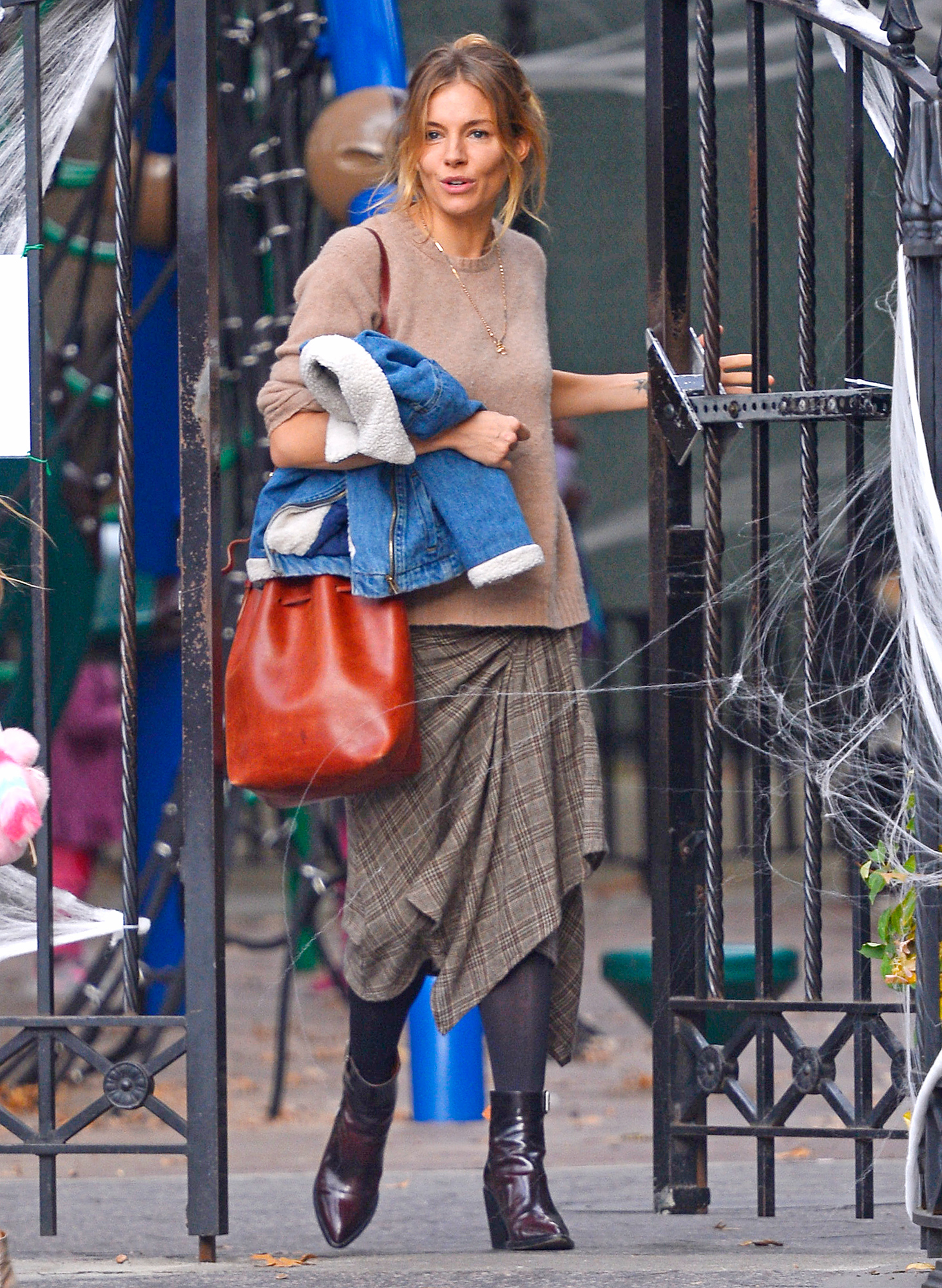 Sienna Miller shows her quirky  fashion style by wearing an assymetrical plaid skirt, cashemere top and brown leather boots