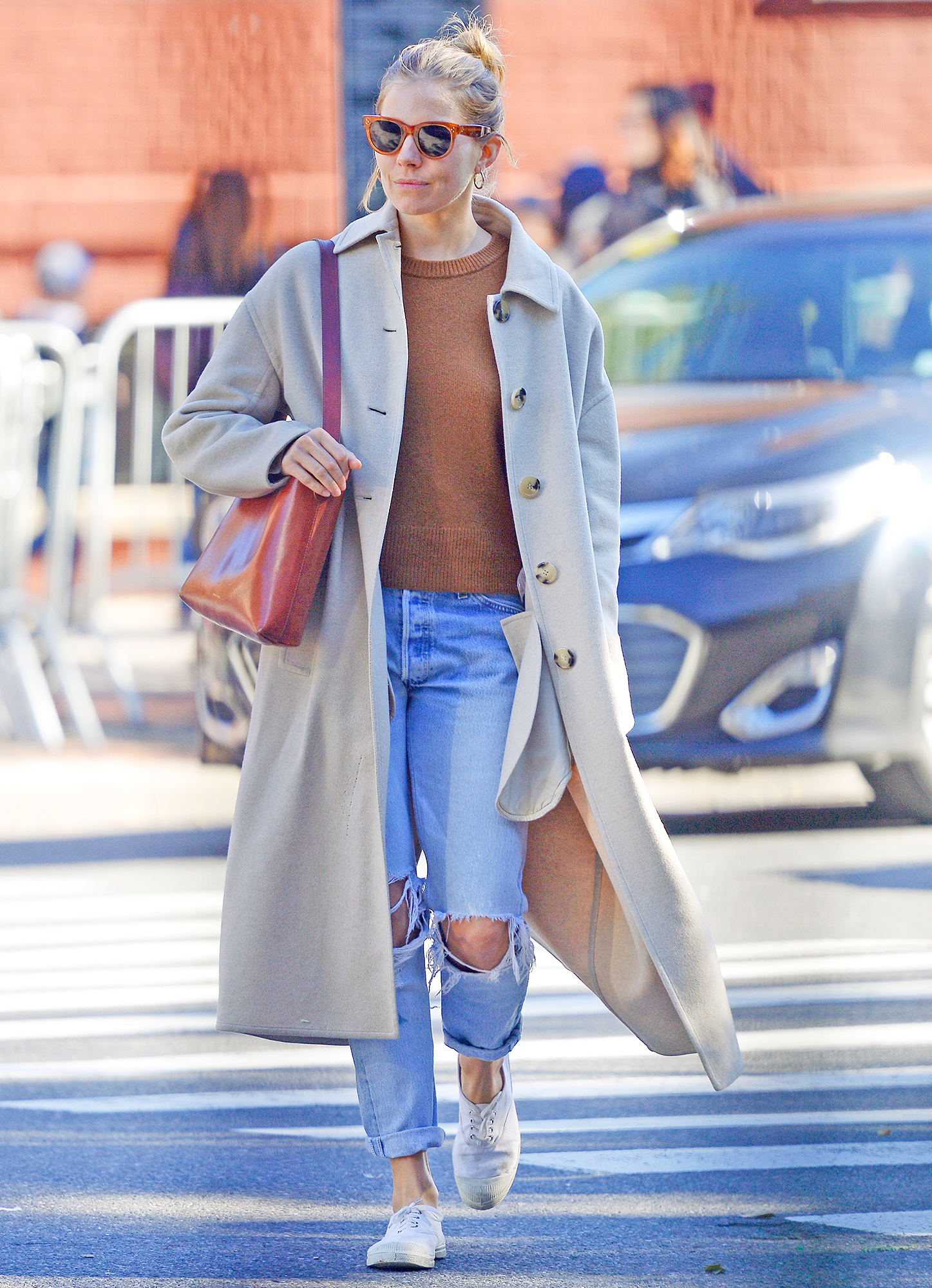 EXCLUSIVE: Sienna Miller wears a pumpkin colored ribbed top, beige wool coat, ripped denim and white sneakers while out and about in New York City