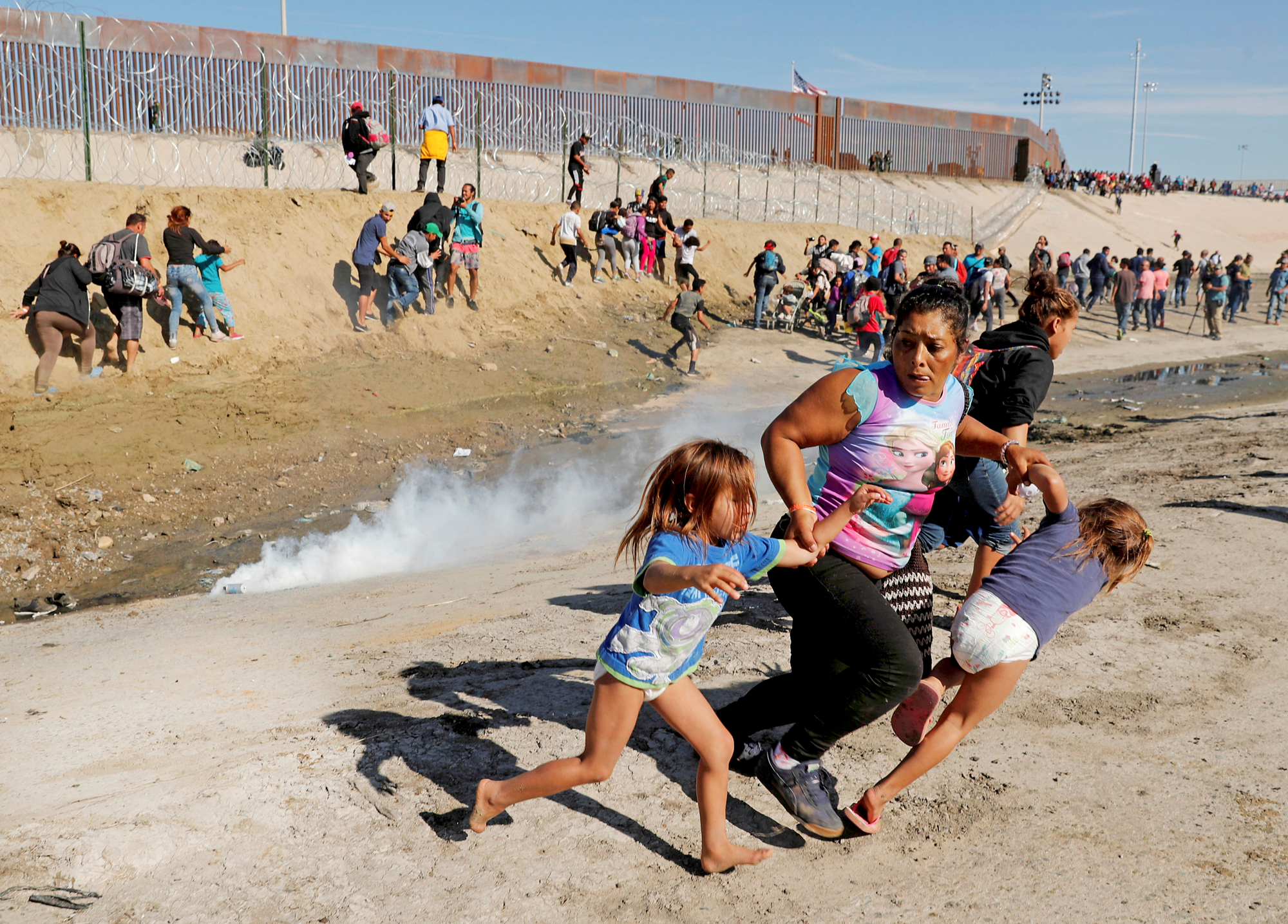 A migrant family runs away from tear gas in front of the border wall between the U.S and Mexico, in Tijuana
