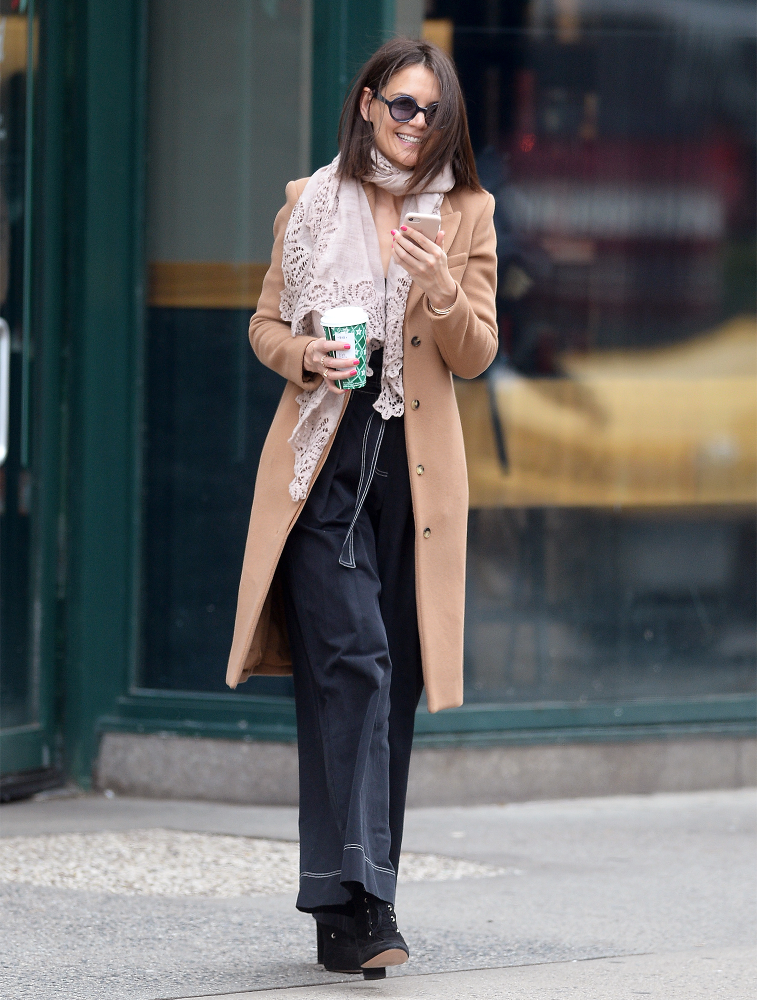 EXCLUSIVE: Katie Holmes is all smiles looking distracted while reading a text on her cellphone while getting her morning coffe in New York City after celebrating Christmas