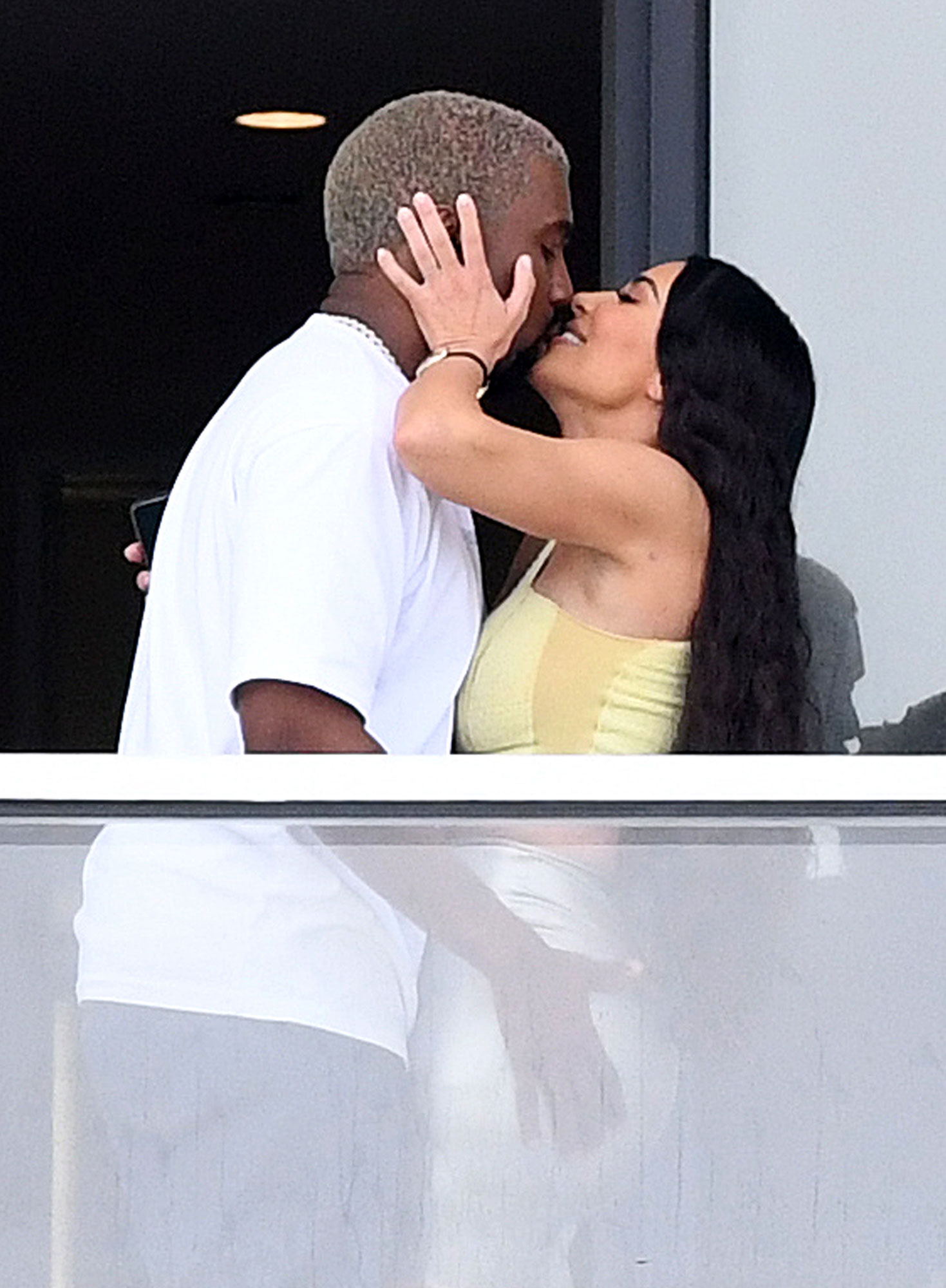 Kim Kardashian and Kanye West share a passionate kiss on their new balcony at the Faena House condo in MiamiBeach