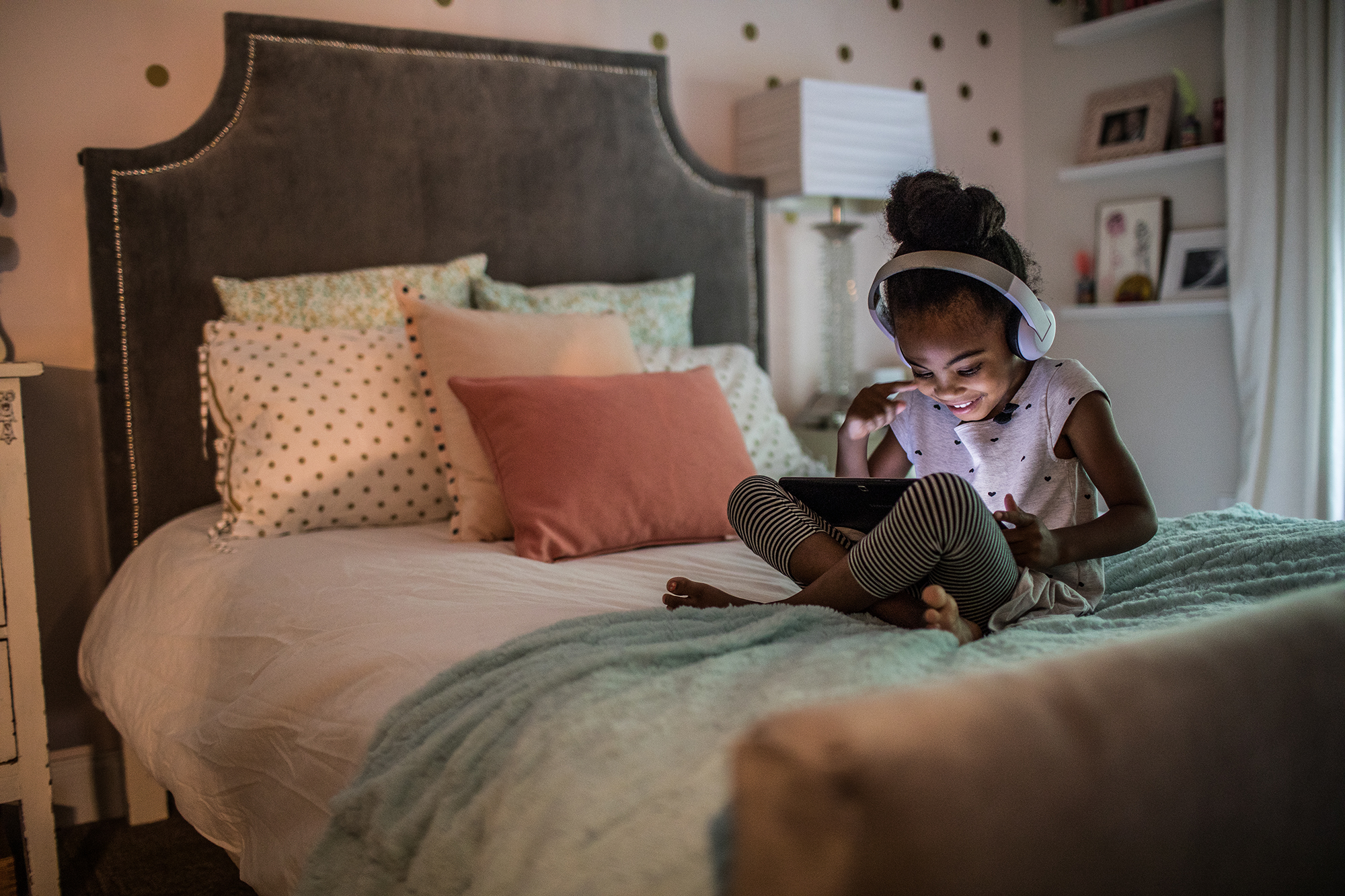 Young girl (6yrs) on couch using tablet
