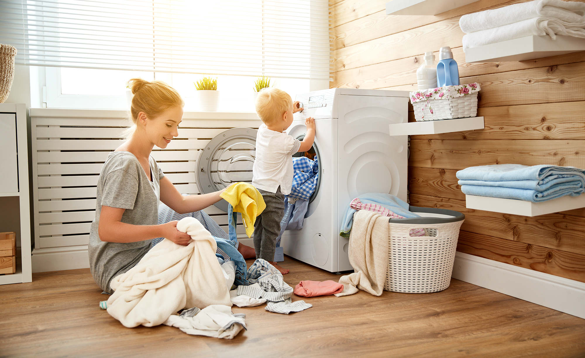 Happy family mother   housewife and children in   laundry load washing machine