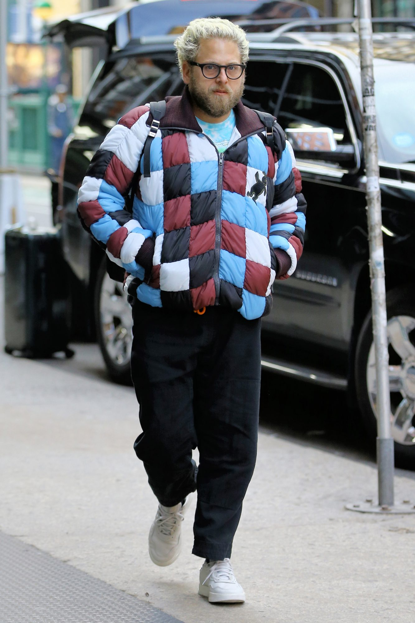 EXCLUSIVE: Blonde-haired style icon and actor Jonah Hill, wearing a colorful patch quilt jacket, arrives home in Soho in New York City on January 28, 2019.