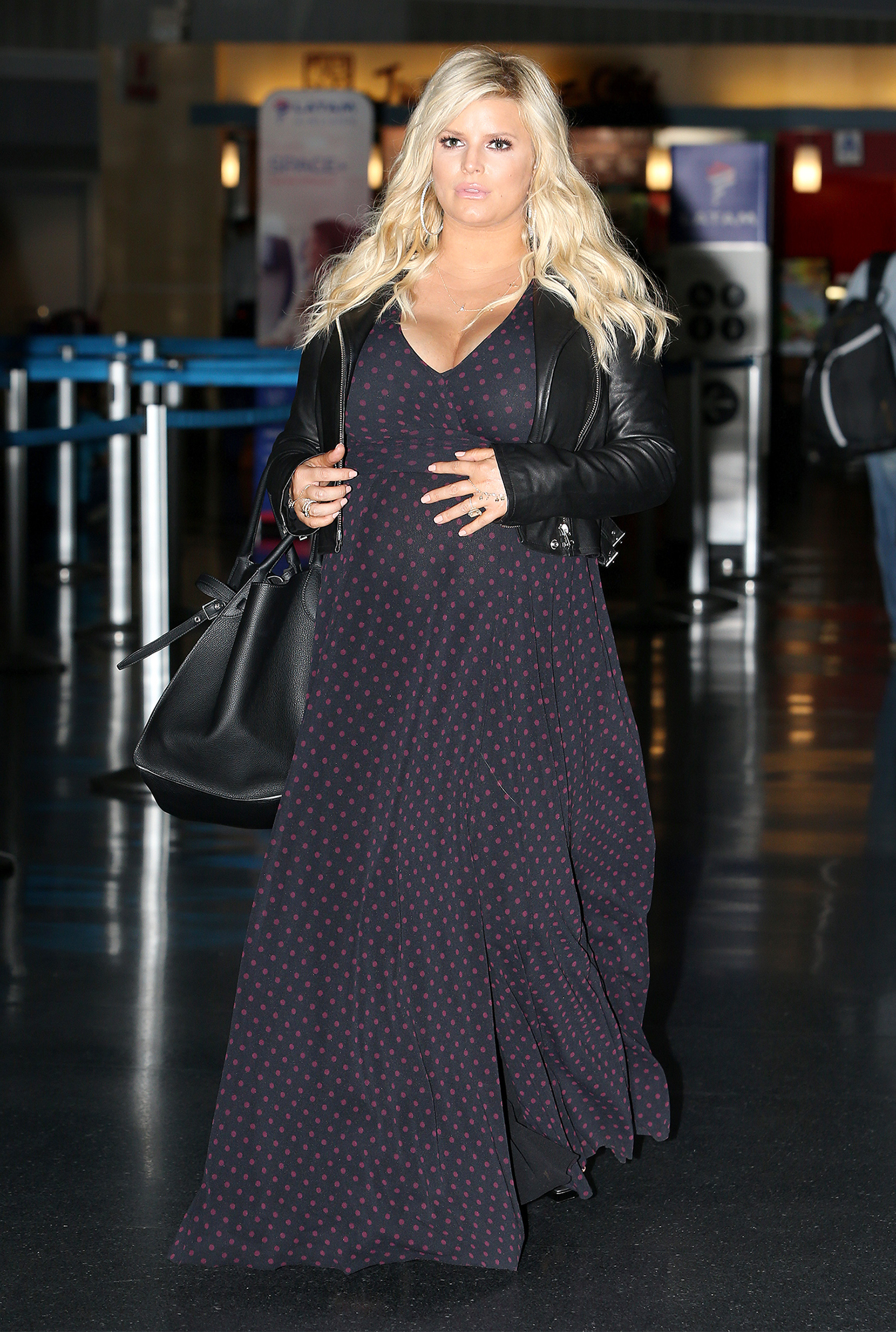 EXCLUSIVE: Jessica Simpson is Spotted Holding Her Baby Bump While Walking Through JFK Airport in New York City.