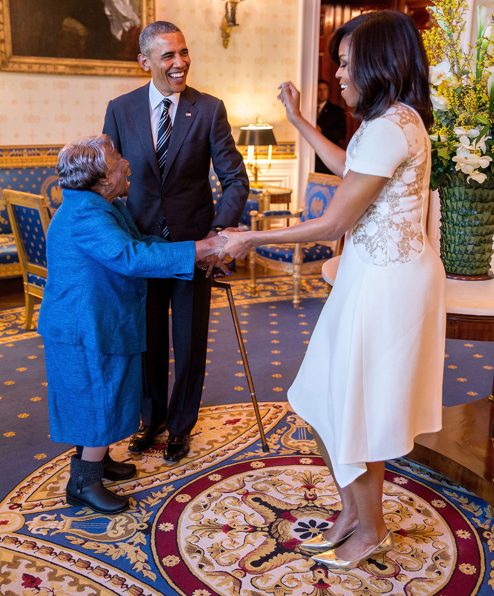 President Barack Obama watches First Lady Michelle Obama dance with 106-Year-Old Virginia McLaurin in the Blue Room of the White House prior to a reception celebrating African American History Month, Feb. 18, 2016. (Official White House Photo by Pete Souza) This official White House photograph is being made available only for publication by news organizations and/or for personal use printing by the subject(s) of the photograph. The photograph may not be manipulated in any way and may not be used in commercial or political materials, advertisements, emails, products, promotions that in any way suggests approval or endorsement of the President, the First Family, or the White House.
