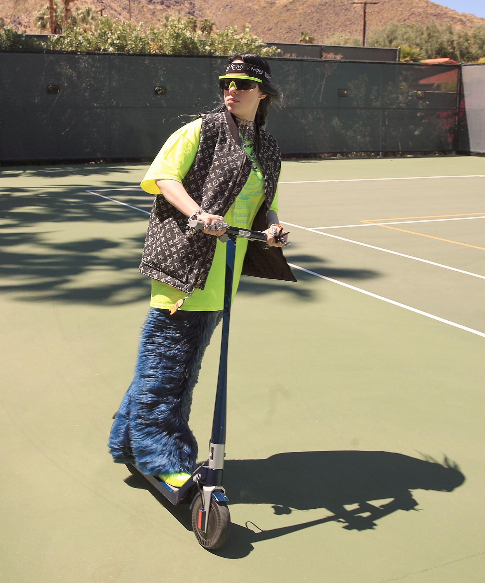 Billie Eilish rides a scooter on the tennis court at the 5th annual Interscope Coachella party.