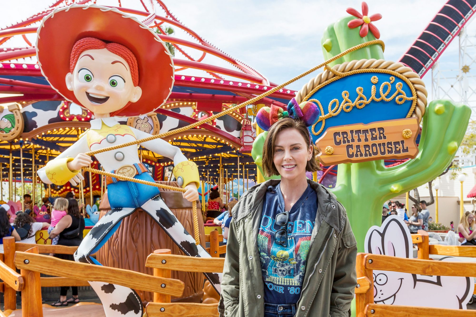 Actress Charlize Theron Poses in Front of Jessie's Critter Carousel at Disney California Adventure Park