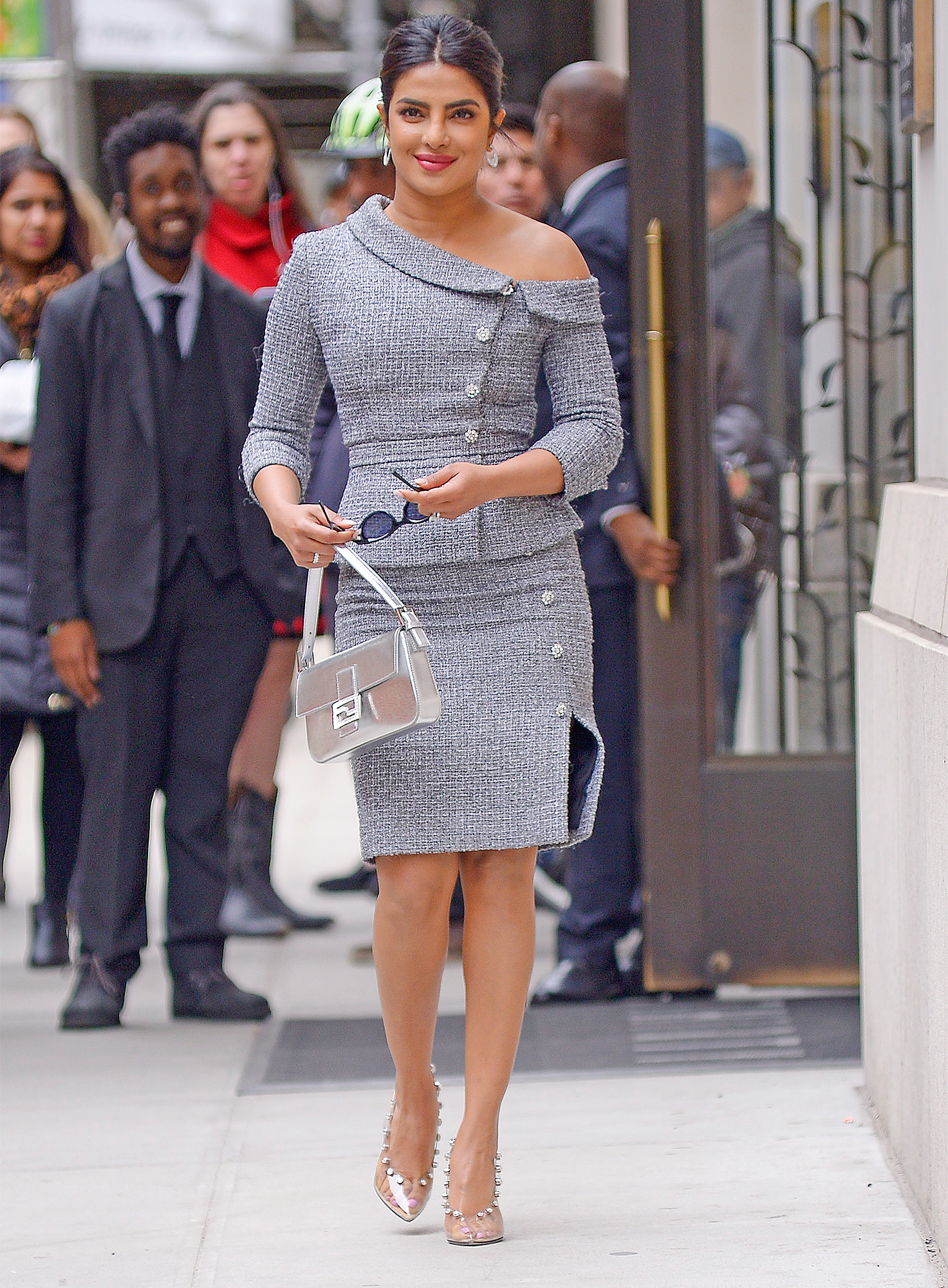 Priyanka Chopra wears a body hugginhg assymetrical dress and silver bag while heading to Women In The World summit in New York CIty