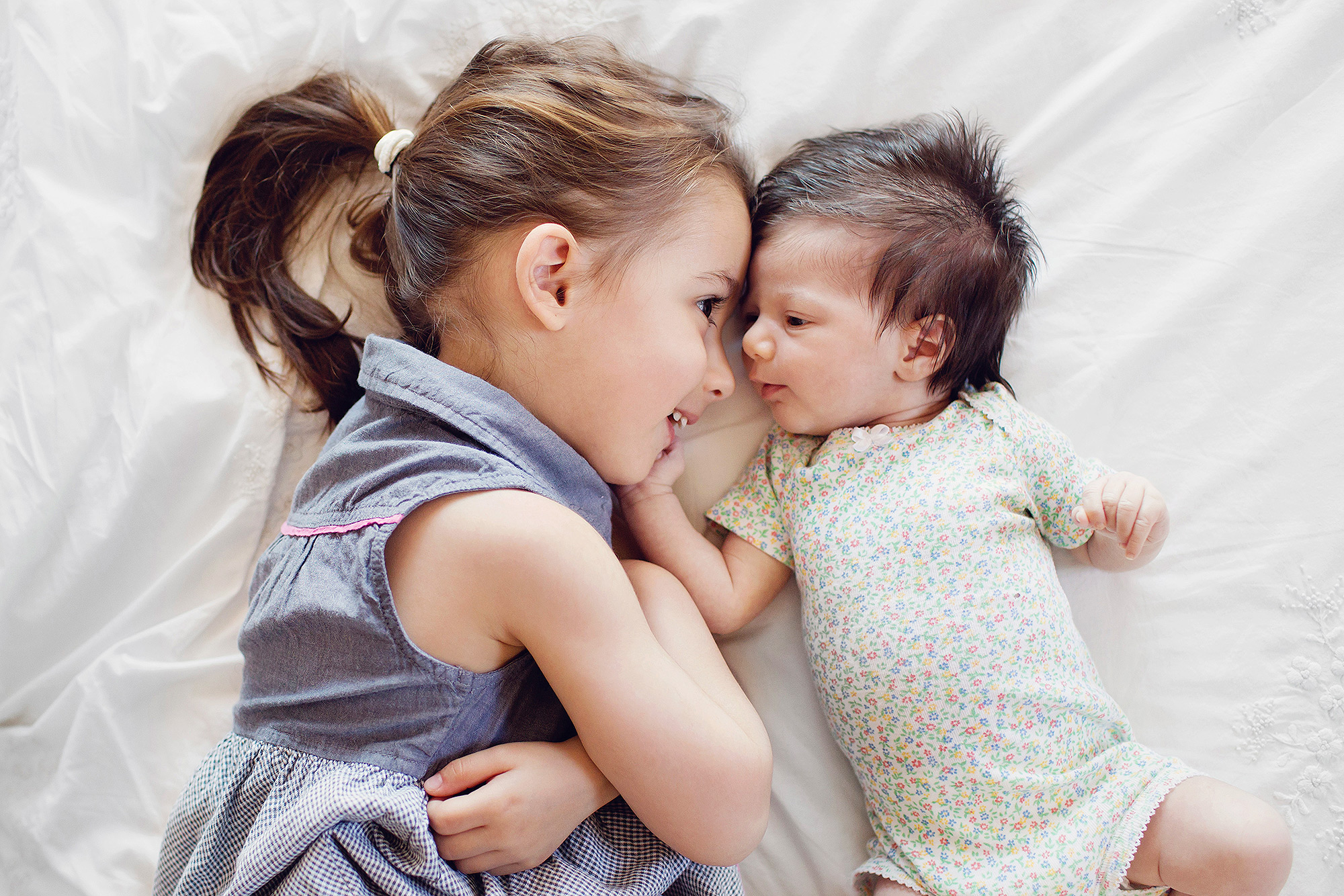 High angle view of girl with ponytail and newborn baby girl lying on a bed.