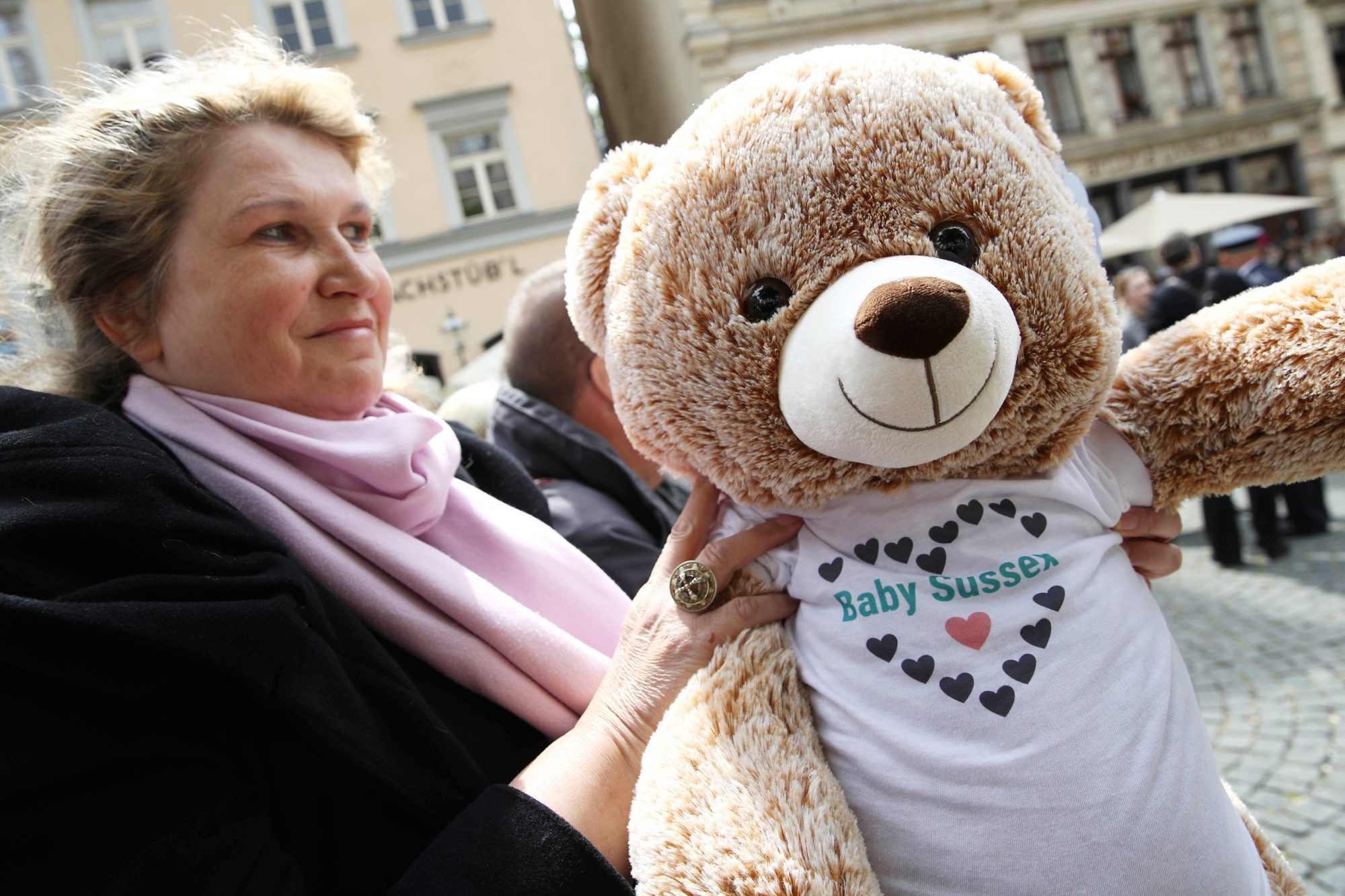 A well wisher holds a teddy bear wearing a t-shirt saying 'Baby Sussex' ahead of the arrival of Camilla, Duchess of Cornwall at St. Thomas Church on May 8, 2019 in Leipzig, Germany.