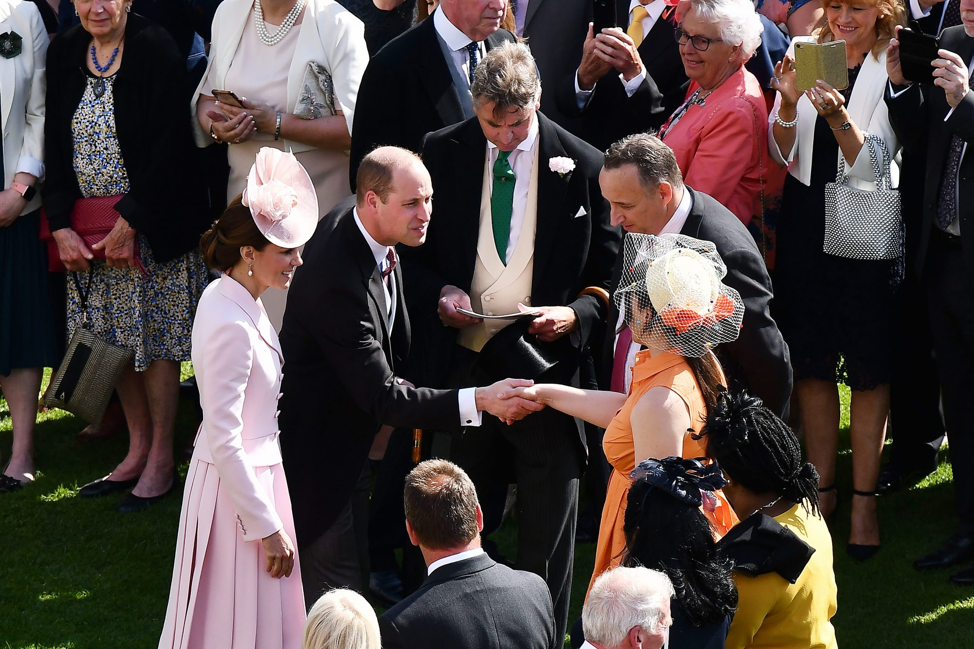 Britain's Prince William, Duke of Cambridge, (C) and Britain's Catherine, Duchess of Cambridge, (L) meet guests at a garden party in the grounds of Buckingham Palace in central London on May 21, 2019