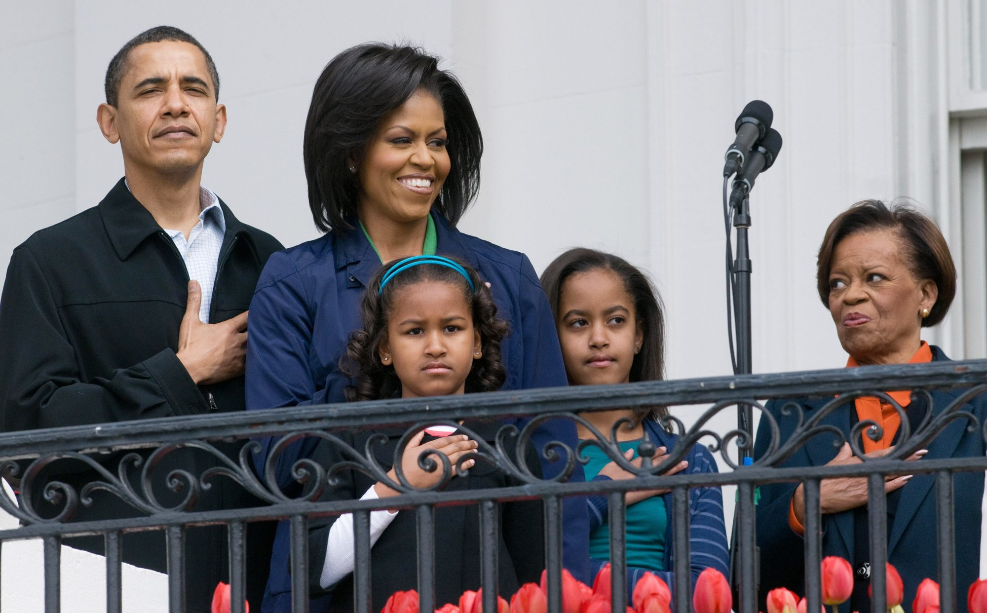 Barack Obama stands alongside First Lady Michelle Obama, their daughters Sasha and Malia and Marian Robinson (R), Michelle's mother, for the National Anthem during the annual White House Easter Egg Roll on the South Lawn of the White House in Washington, DC, on April 13, 2009.