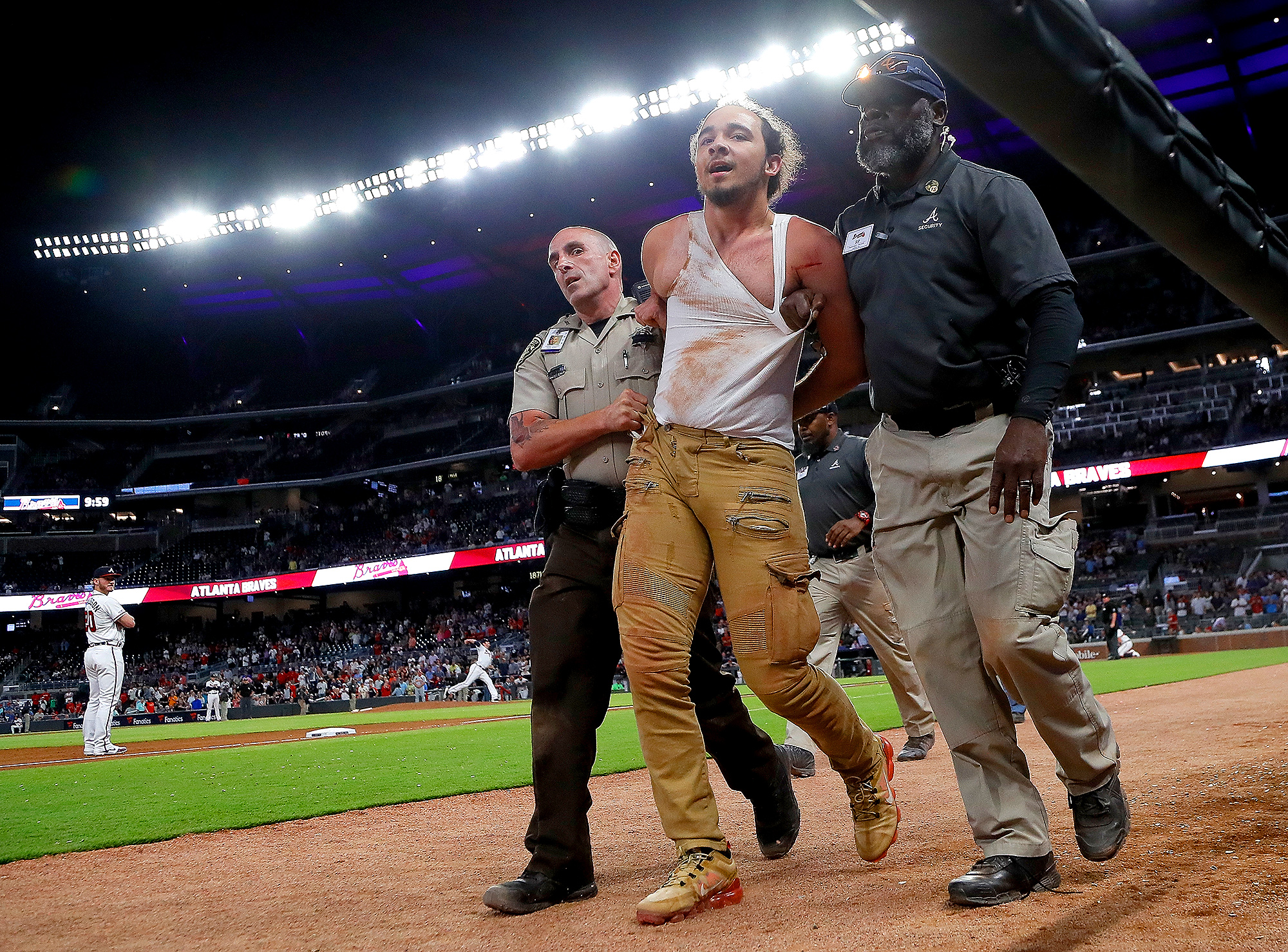 spectator is escorted out by security after he ran on the field in Atlanta, Georgia