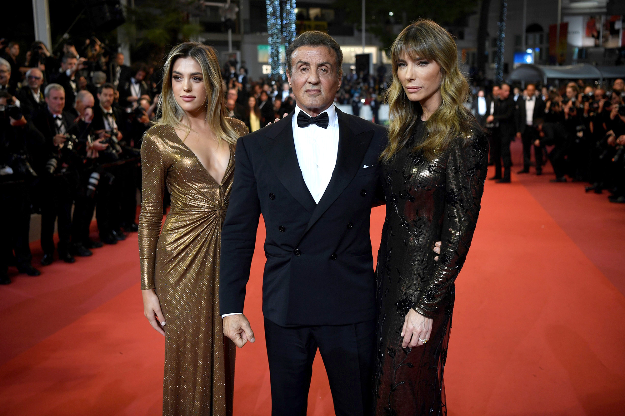 """US actor Sylvester Stallone (C) poses with his wife Jennifer Flavin (R) and daughter Sistine as they arrive for the screening of """"Homage to Sylvester Stallone - Rambo : First Blood"""" at the 72nd edition of the Cannes Film Festival in Cannes, southern France, on May 24, 2019. (Photo by CHRISTOPHE SIMON / AFP) (Photo credit should read CHRISTOPHE SIMON/AFP/Getty Images)"""