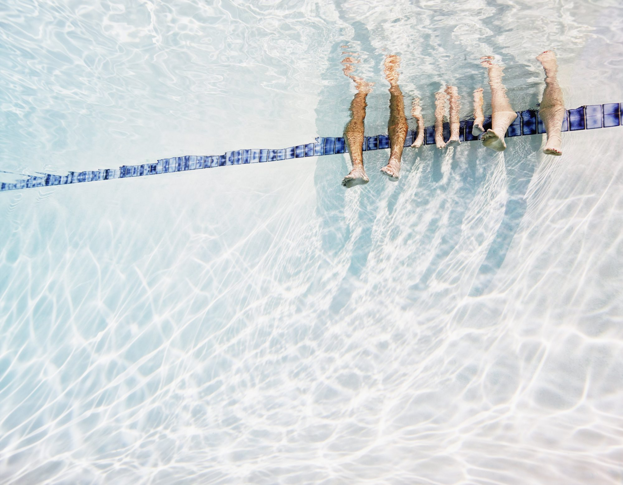 Family's feet hanging in swimming pool