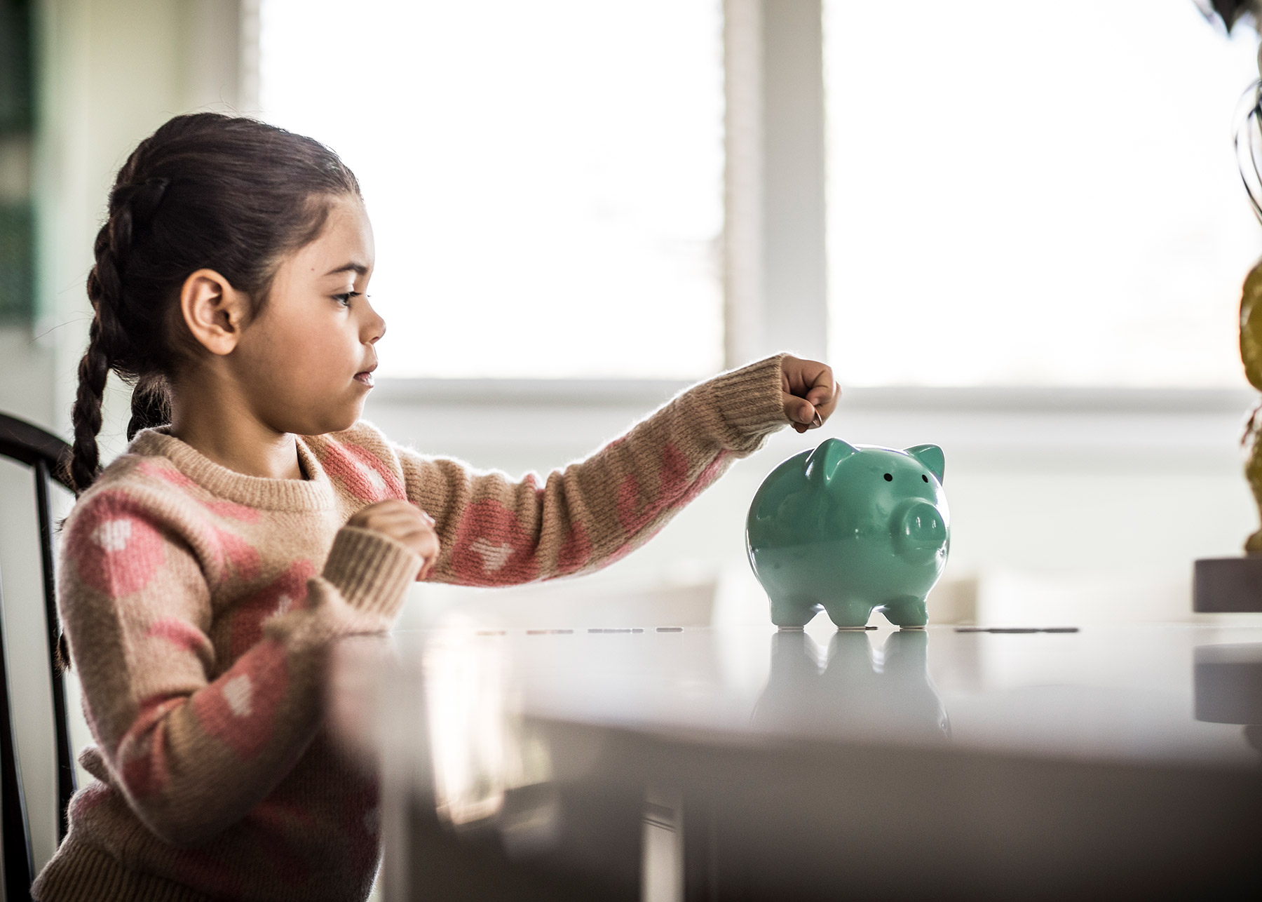 Girl (7 yrs) putting money in piggybank