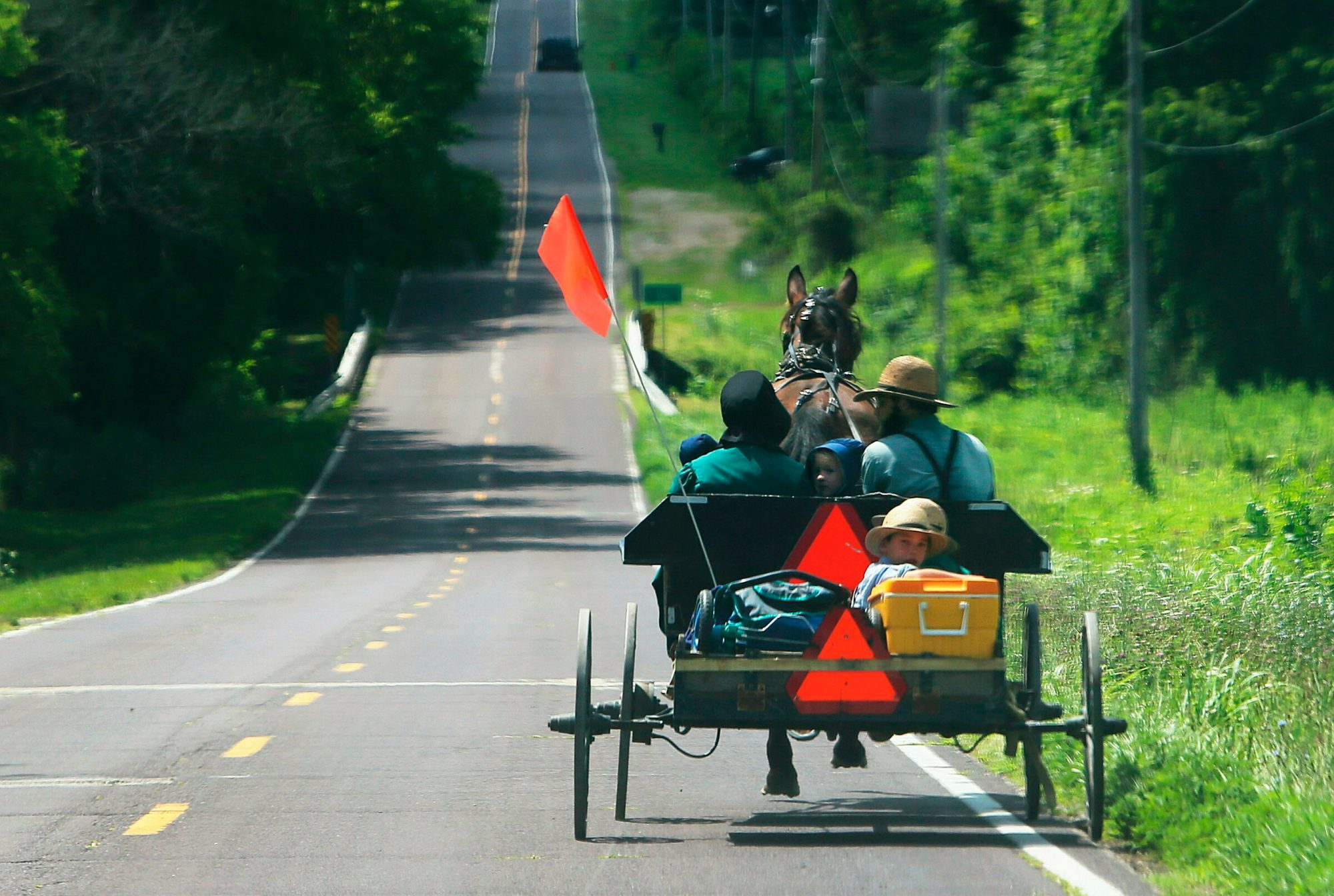 A buggy with six people goes southbound past the spot on Highway OO where a buggy accident occurred on Thursday, July 11, 2019, in St. Francois County south of Farmington, Mo. A buggy going northbound was struck by a pickup truck just south of the Liberty Blueberry Farms. An eight-year-old boy was killed in the accident and four people were seriously injured. (J.B. Forbes/St. Louis Post-Dispatch via AP)