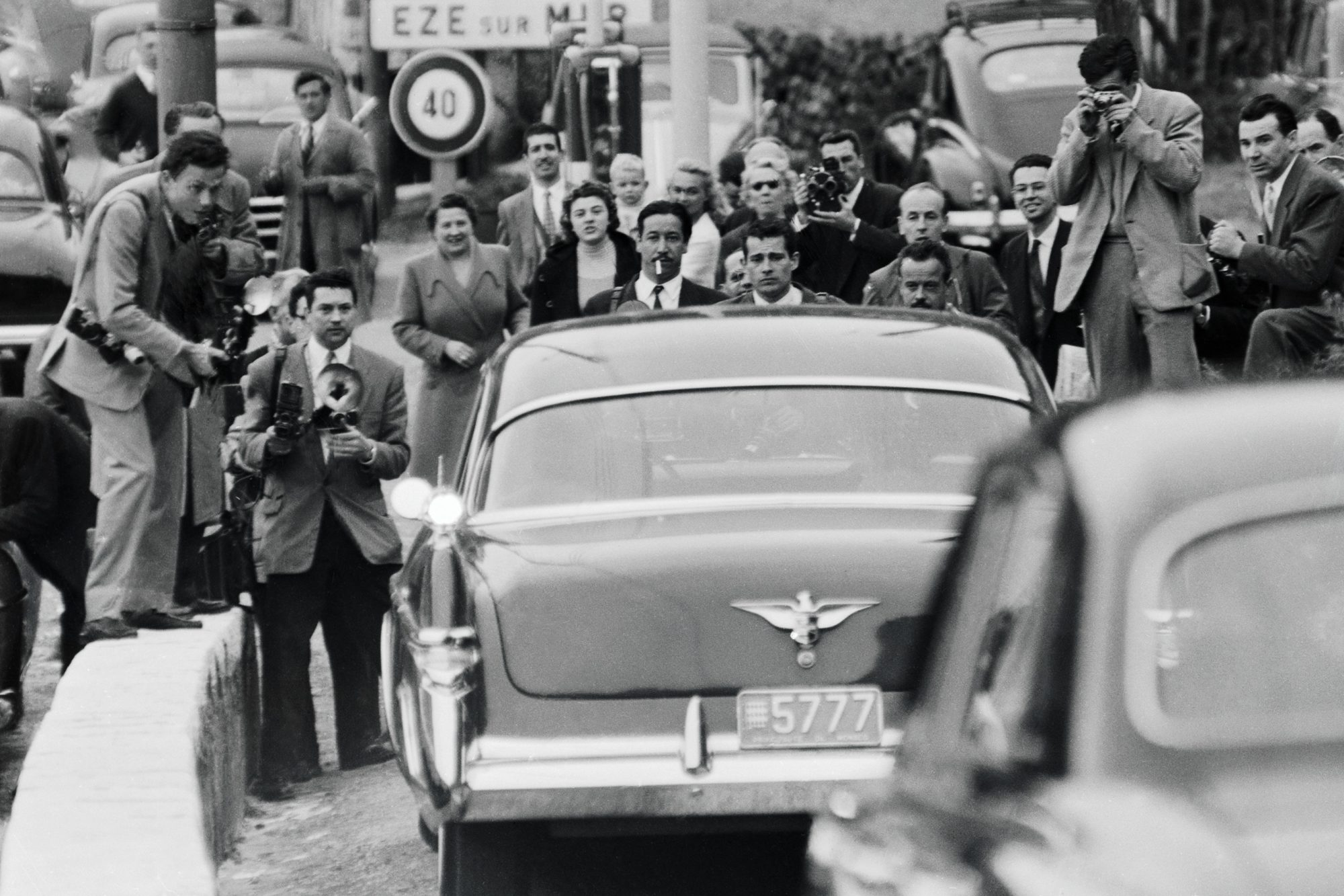 """(Original Caption) Photographers form a human barricade across a road in France in an attempt to photograph Prince Rainier III and Grace Kelly as they rode back to the principality. The incident occurred when the Prince was driving Miss Kelly back from a luncheon in Cap Ferrat. After the couple returned to the palace, Rainier's press chief denounced the photographers' activities as """"intolerable,"""" and all press photographers were barred from the April 18th civil wedding because of the incident."""