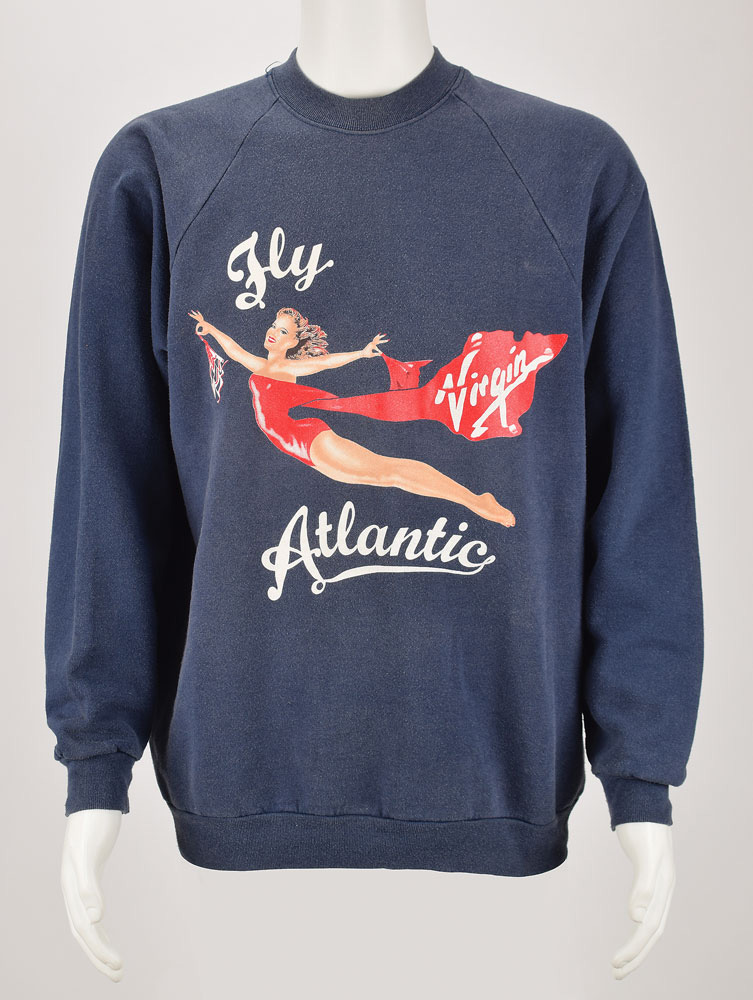 """Princess Diana's personally-owned- and -worn Virgin Atlantic sweatshirt given to her by business magnate Richard Branson, which Diana later presented to her longtime personal trainer, Jenni Rivett. The dark blue cotton/polyester sweatshirt, no size but likely medium/large, features a screen-printed image of the Virgin Atlantic 'Flying Lady' logo with white cursive text: """"Fly Atlantic."""" Included with the sweatshirt is a small 4 x 2.75 gift tag bearing an ANS from Princess Diana, which reads: """"Dearest Jenni, Lots of love from, Diana, x."""" In fine condition, with expected wear from use. https://www.rrauction.com/bidtracker_detail.cfm?IN=247 Credit: RR Auction"""