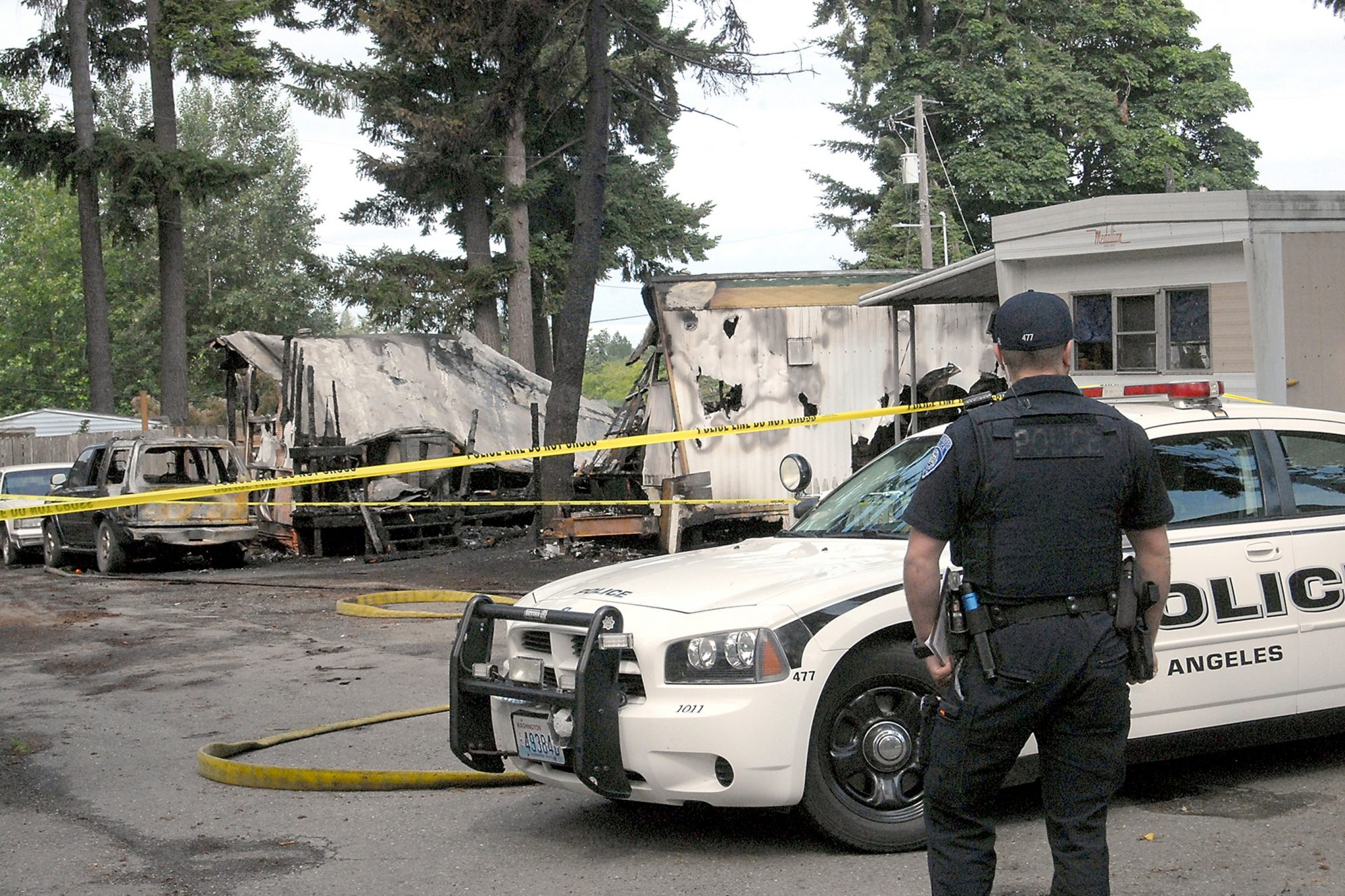 Port Angeles police Officer T.J. Mueller looks over the scene of a fire that destroyed two mobile homes and left several dead early Saturday, July 6, 2019, at the Welcome Inn RV Park in Port Angeles, Wash
