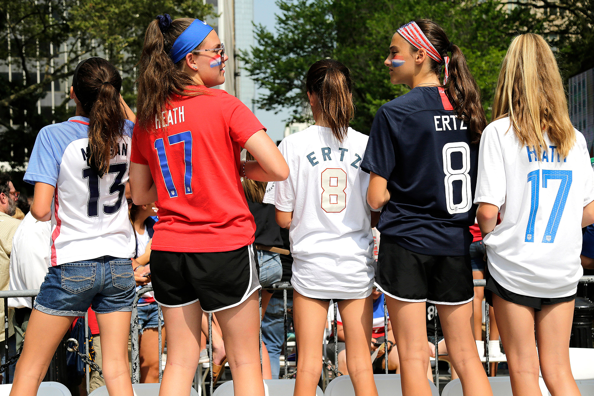 Girls in soccer jerseys wait for the arrival of the U.S. women's soccer team at City Hall,