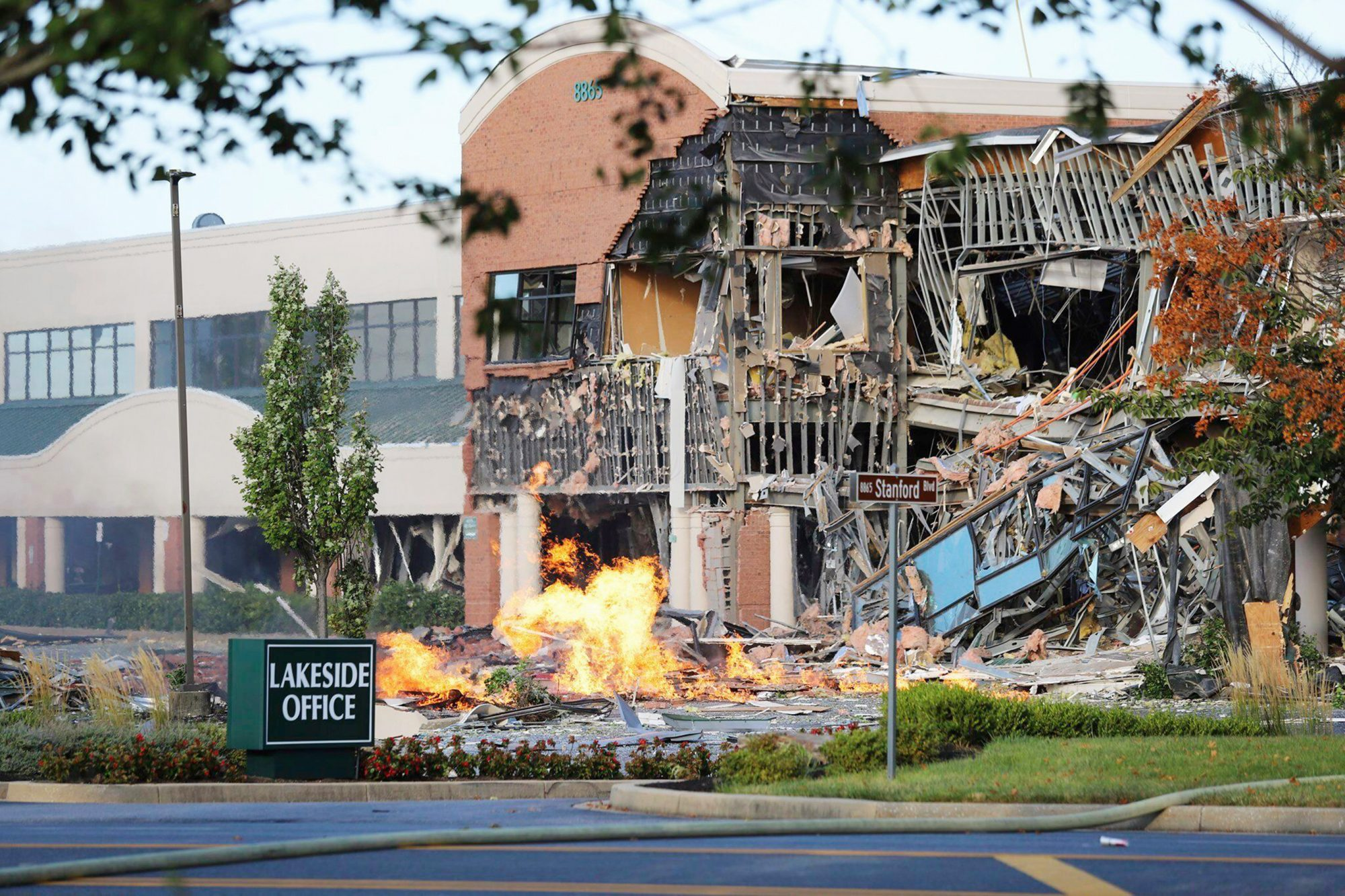 This photo provided by the Howard County Fire And Rescue shows the scene of a damaged building and burning debris nearby after an explosion at an office complex and shopping center in Columbia, Md Gas Explosion Maryland, Columbia, USA - 25 Aug 2019