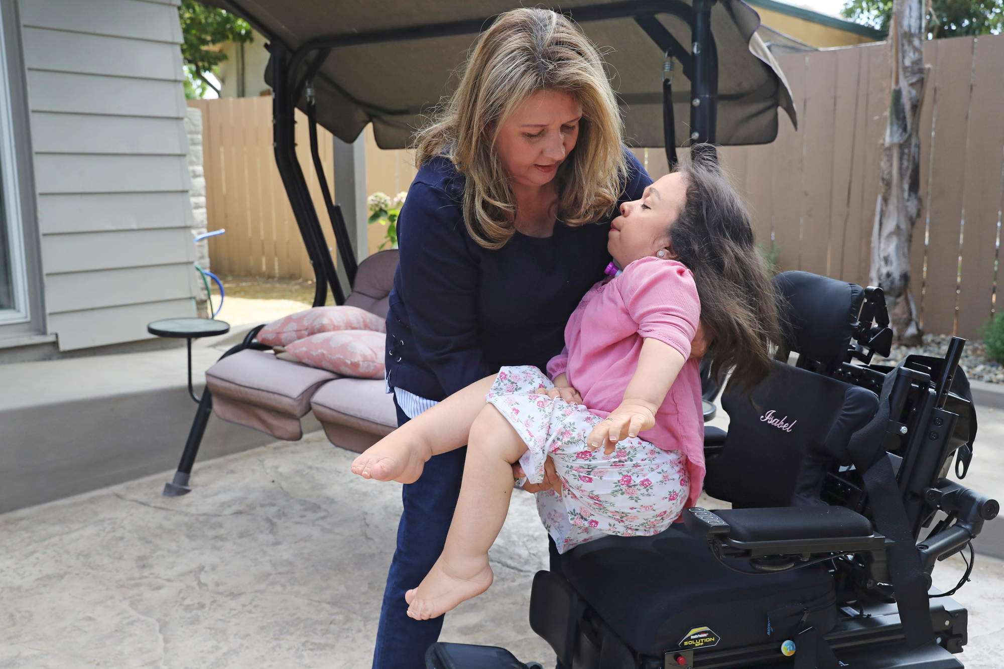Karla Bueso lifts her daughter, Maria Isabel Bueso, 24, back into her wheelchair at home in Concord, Calif., Aug. 28, 2019. (Jim Wilson/The New York Times)
