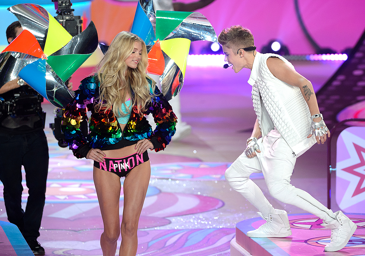 Musician Justin Bieber (R) performs while model Toni Garrn walks the runway during the 2012 Victoria's Secret Fashion Show