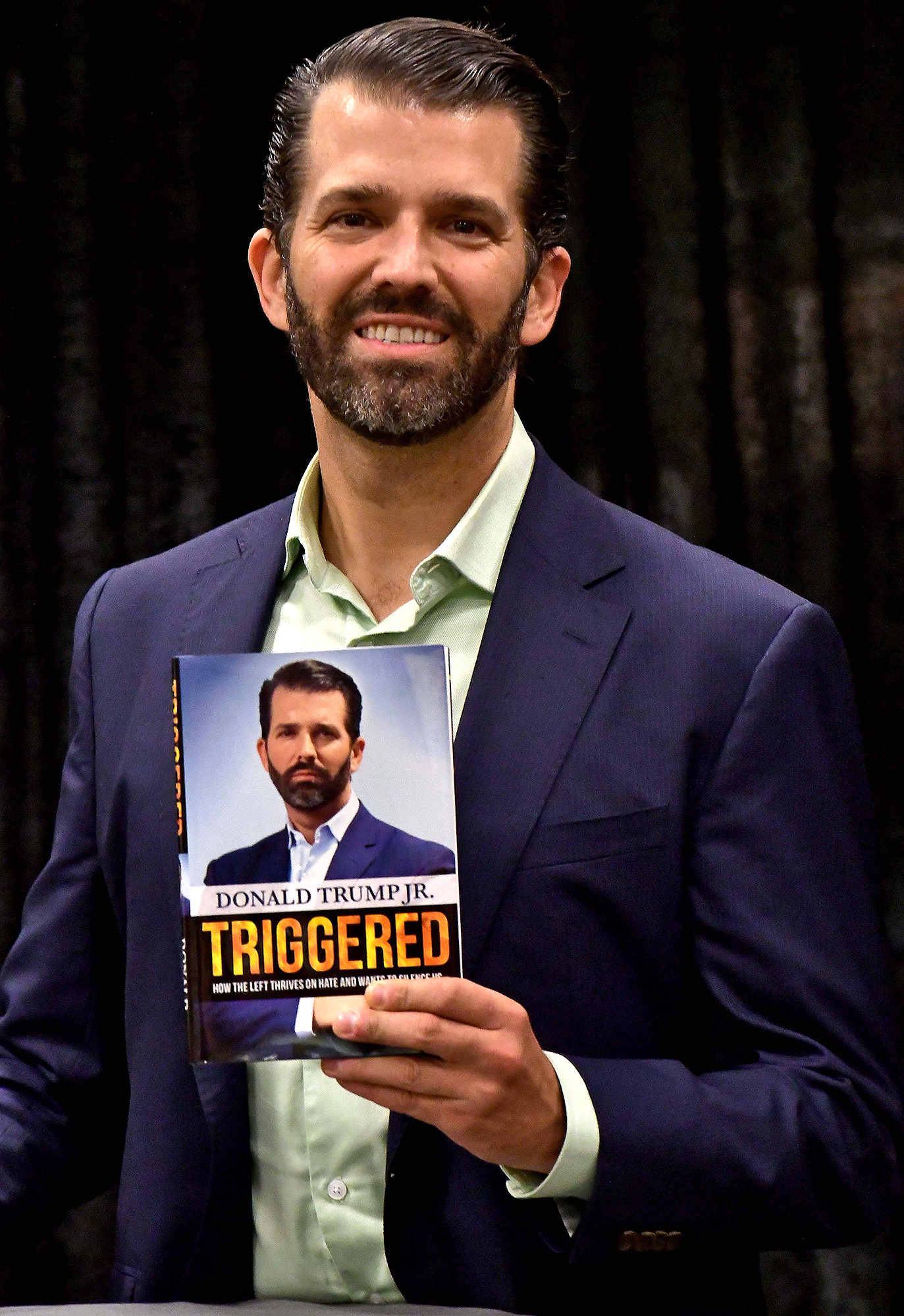 Donald Trump Jnr. with a copy of his book Donald Trump Jnr. 'Triggered'