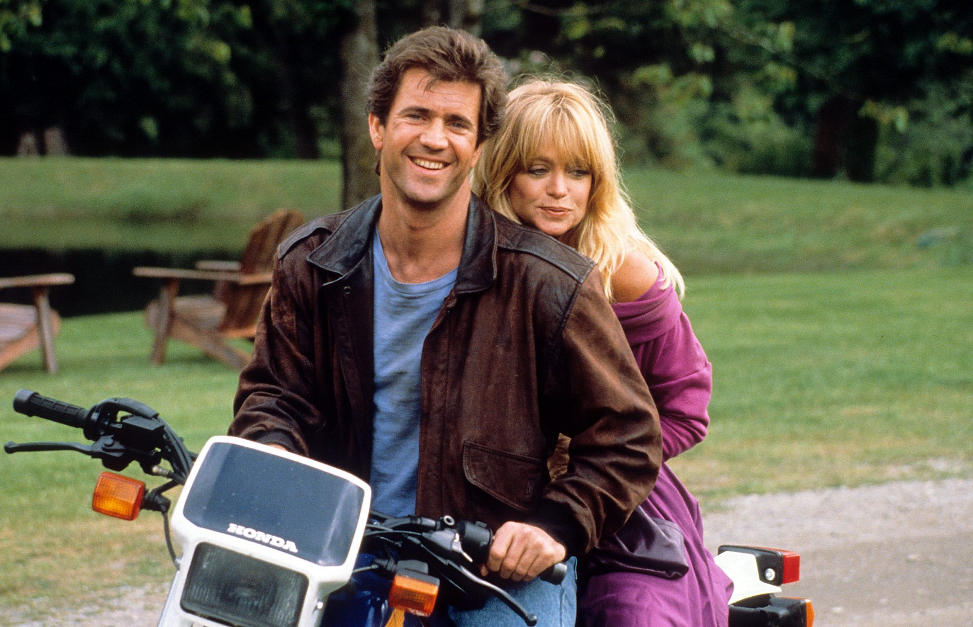 Mel Gibson and Goldie Hawn sitting on a motorcycle together in a scene from the film 'Bird On A Wire', 1990