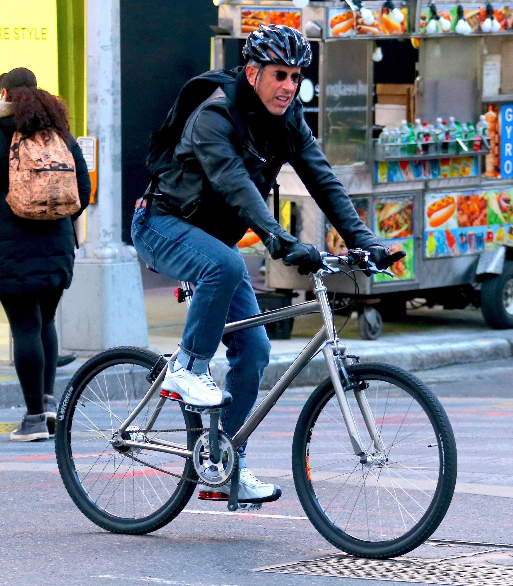 Jerry Seinfeld rides a bicycle in the streets of New York