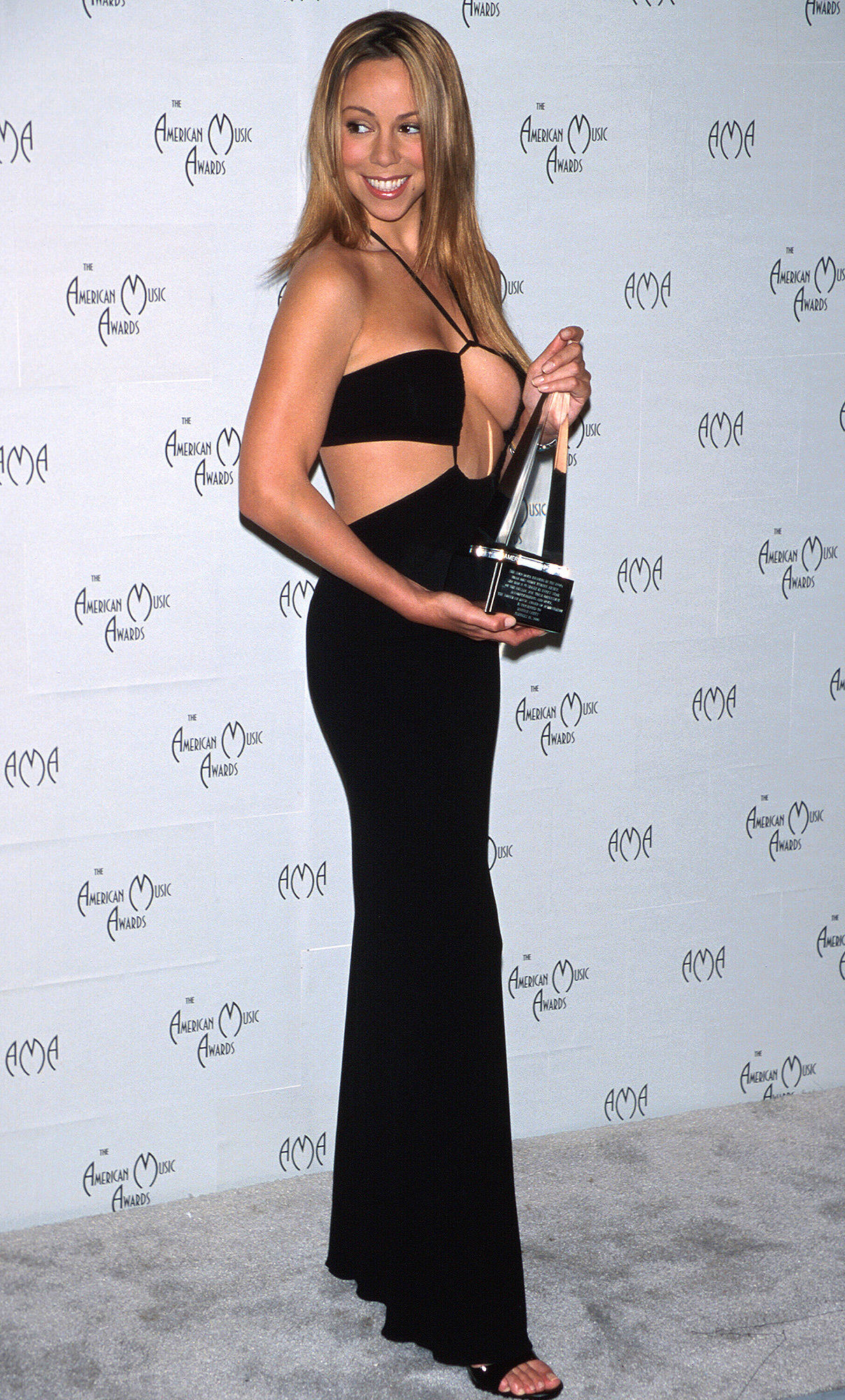 Mariah Carey (wearing black two-piece outfit) holding her award in Press Room at American Music Awards.