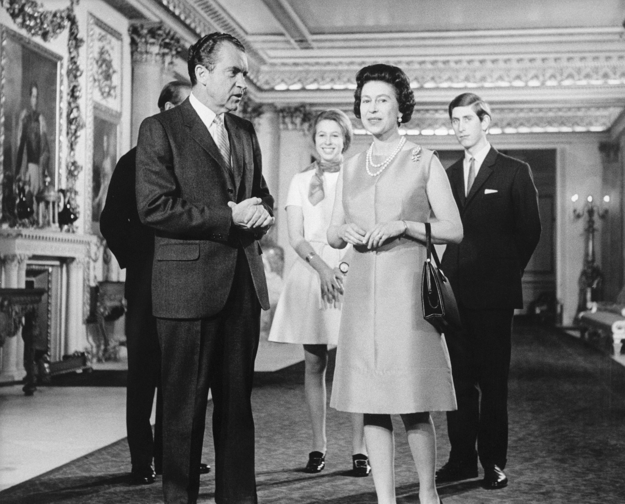President Nixon stands with Queen Elizabeth during a meeting at Buckingham Palace. Princes Charles and Philip stand with Princess Anne behind them.