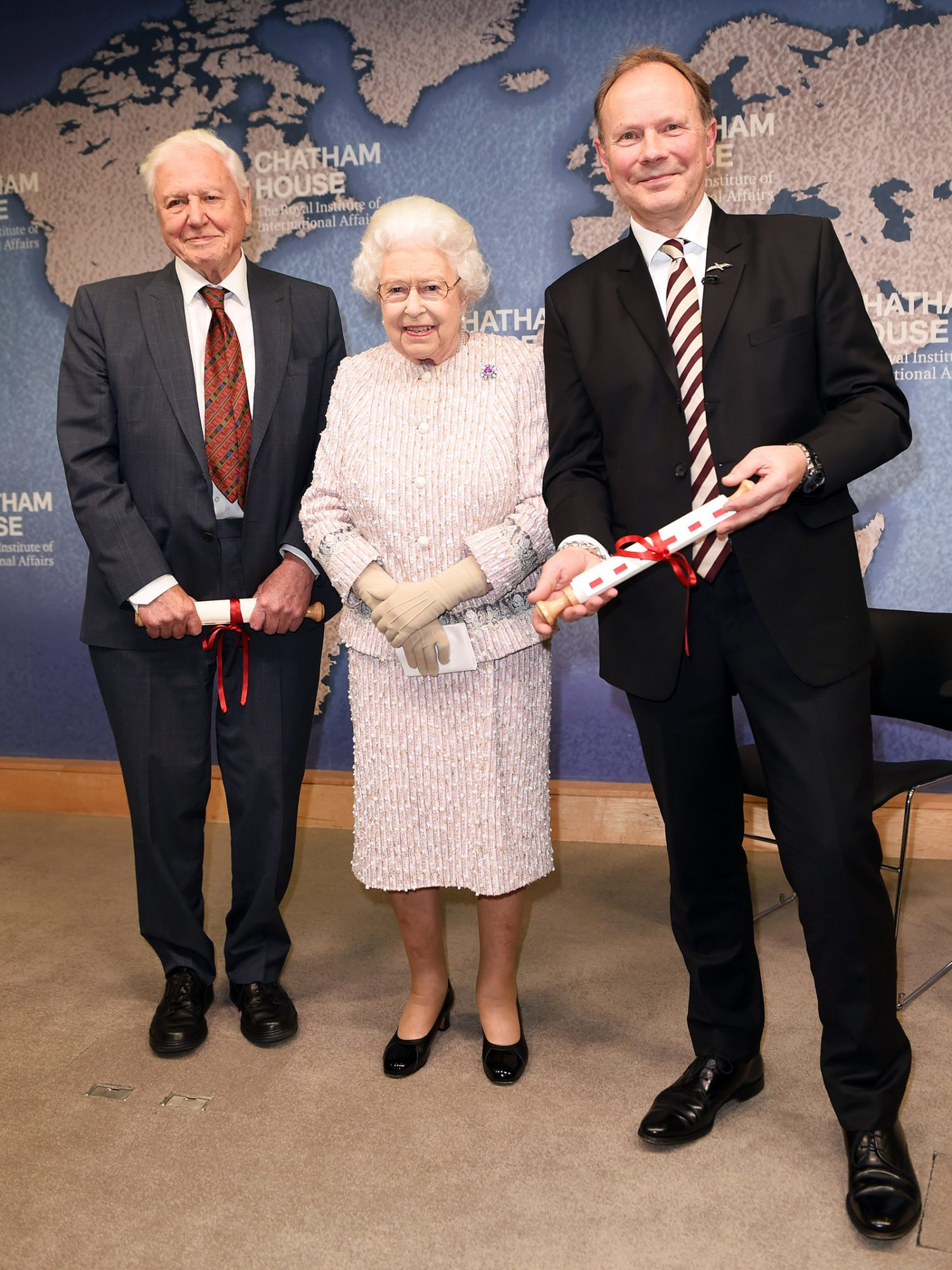 Queen Elizabeth II presents the Chatham House Prize 2019 to Sir David Attenborough (L) and Julian Hector, Head of the BBC Natural History Unit at the Royal institute of International Affairs, Chatham House on November 20, 2019 in London Colney, England