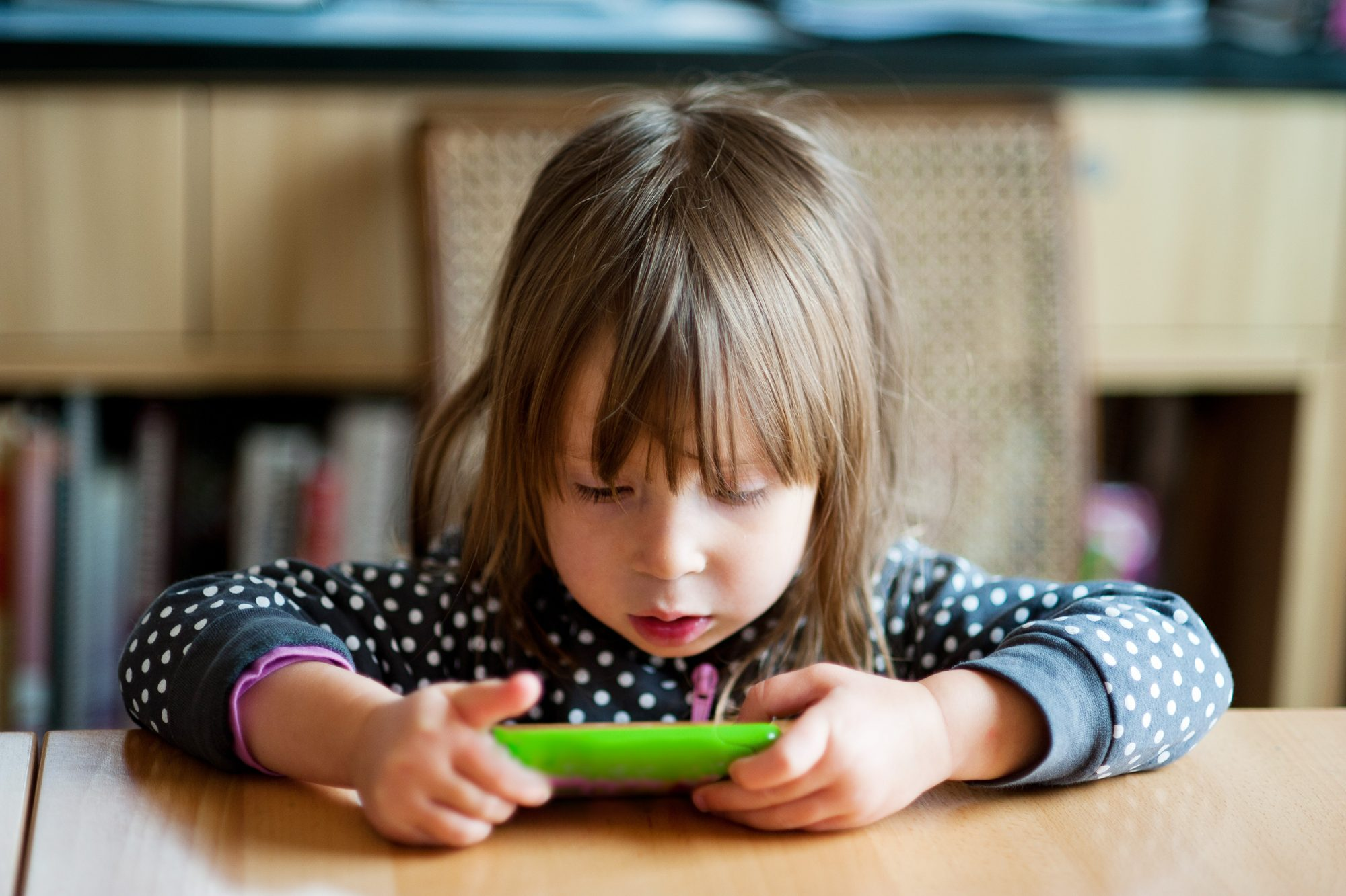 Toddler girl using smartphone at kitchen table at breakfast.