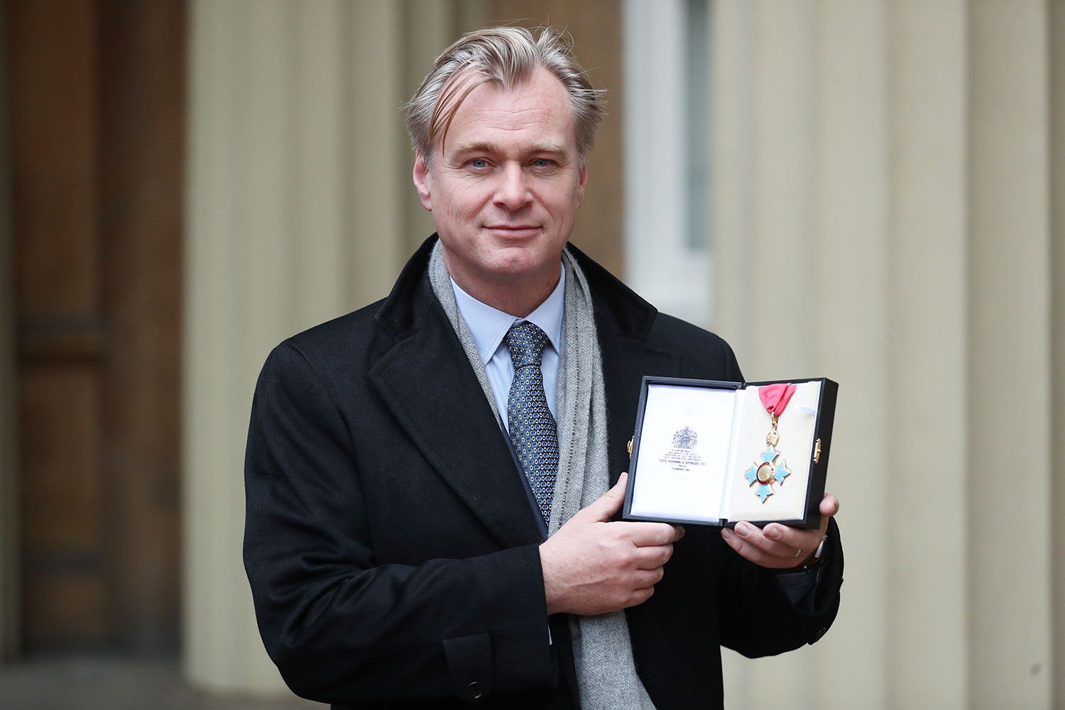 British-American director Christopher Nolan poses with his medal after he was made a Commander of the British Empire (CBE) for services to film during an investiture ceremony at Buckingham Palace, London on December 19, 2019.