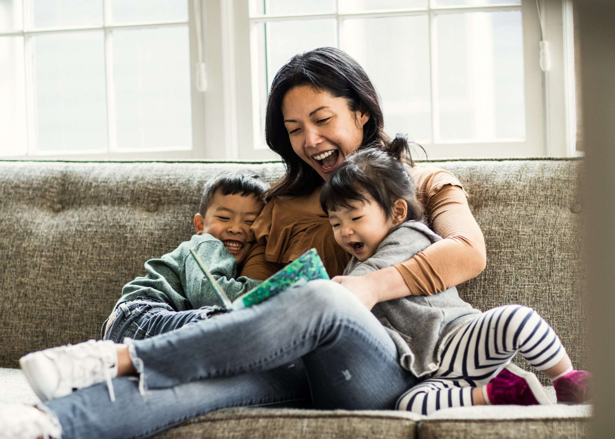 Mother reading to kids on couch