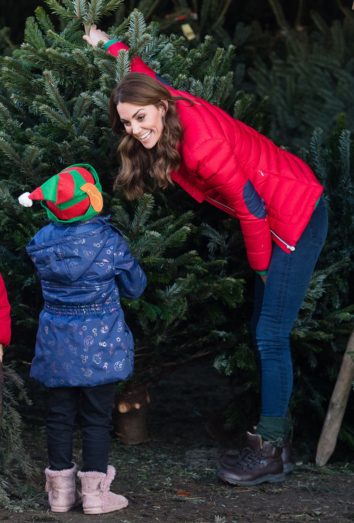 Catherine, Duchess of Cambridge speaks to young children as she helps pick Christmas trees for preschool