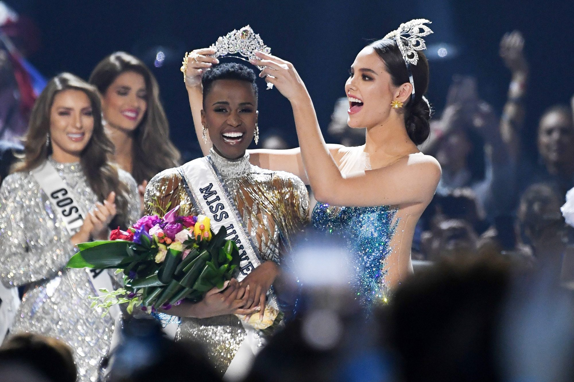 Miss Universe 2018 Philippines' Catriona Gray (R) crowns the new Miss Universe 2019 South Africa's Zozibini Tunzi on stage during the 2019 Miss Universe pageant at the Tyler Perry Studios in Atlanta, Georgia on December 8, 2019