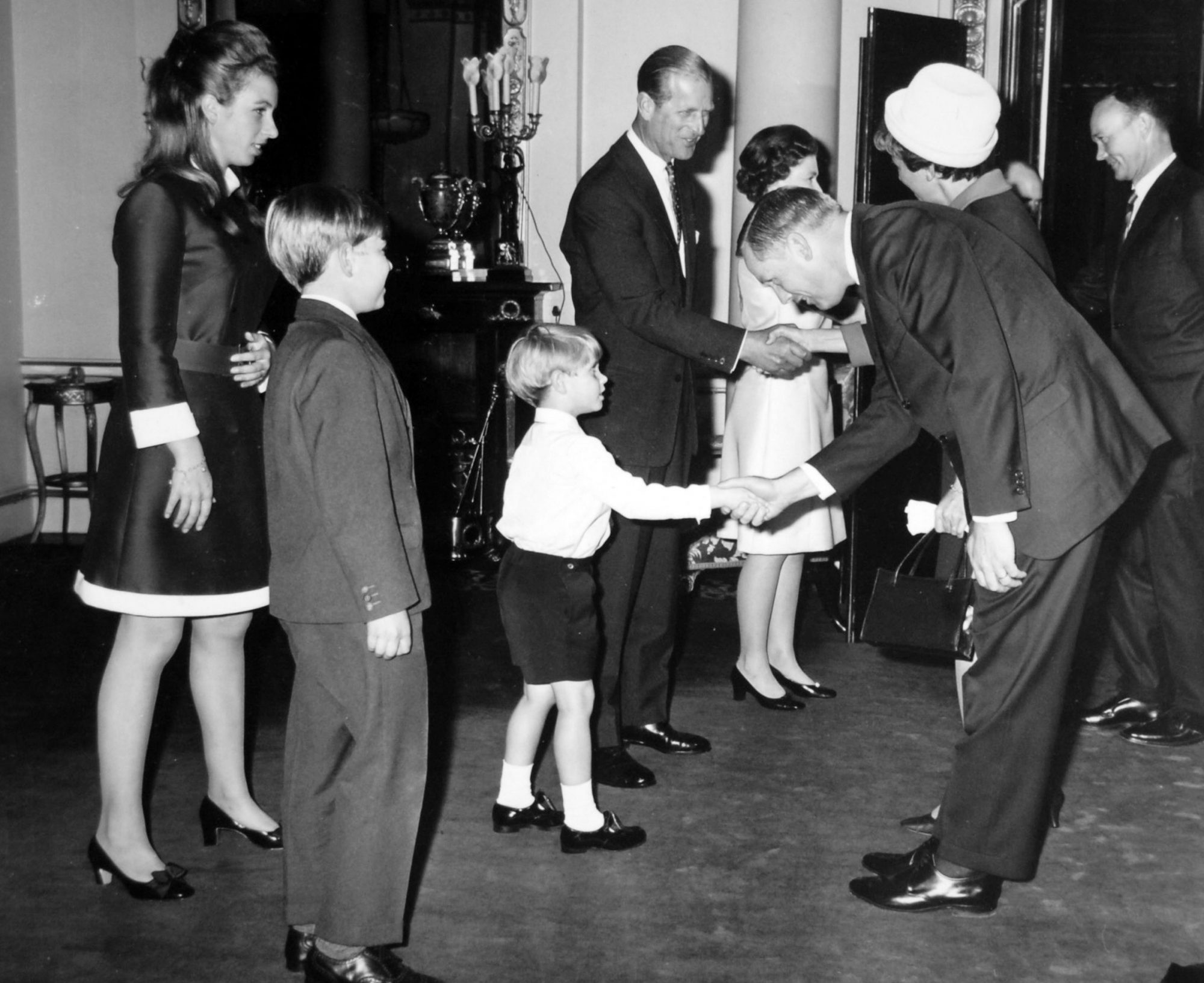 Prince Edward shaking hands with Neil Armstrong, first man to set foot on the Moon at Buckingham Palace during their triumphal world tour. Queen Elizabeth II welcomes Colonel Michael Collins, who orbited in the command module