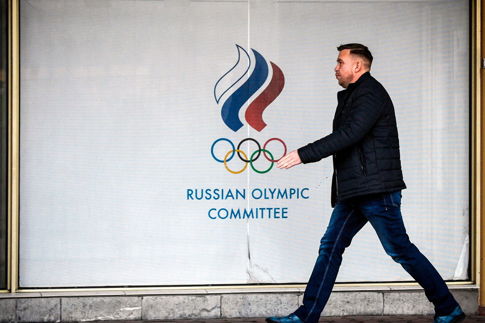 A man walks in front of the Russian Olympic Committee (ROC) headquarters in Moscow on December 6, 2019