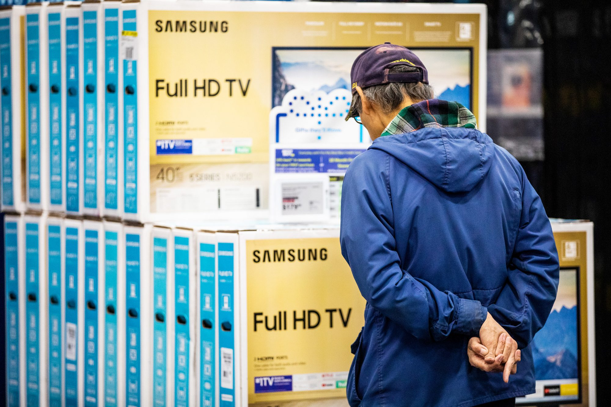 Black Friday shopper looks at televisions at a Best Buy