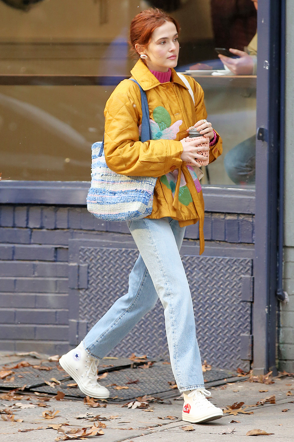 Zoey Deutch leaves a coffee shop with her coffee mug encased by a crocheted warmer as she films 'The Politician' in East Village in New York City.
