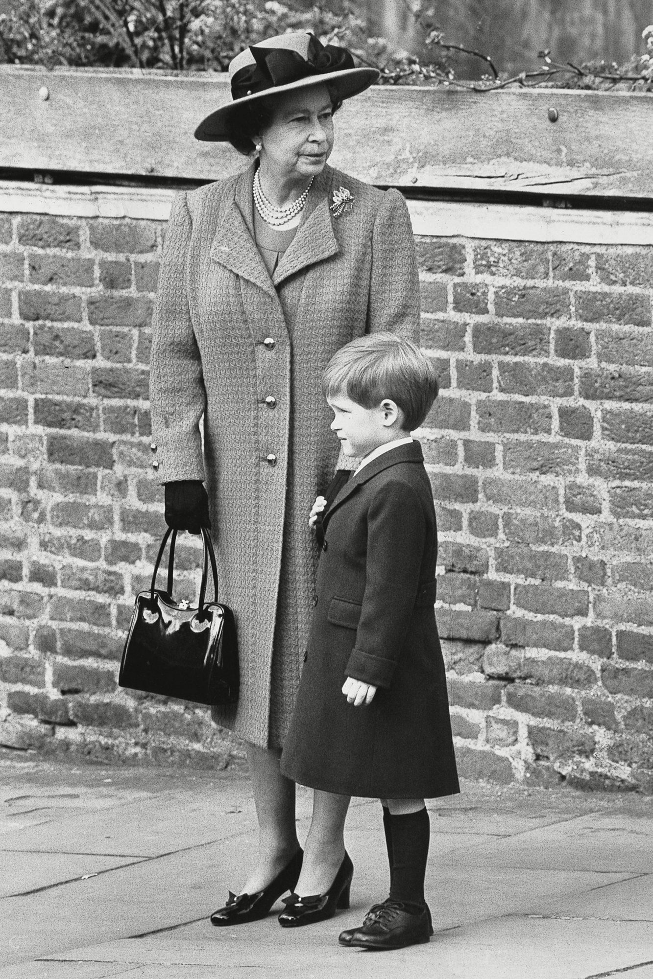 Queen Elizabeth Ii With Her Grandson Prince Harry. Easter Sunday Service At St. Georges Chapel At Windsor Castle. A Proud Young Man Holds Tightly To His Grandmother's Hand After Easter Sunday Morning Srvice. Prince Harry Aged Four Smart In A Maroon