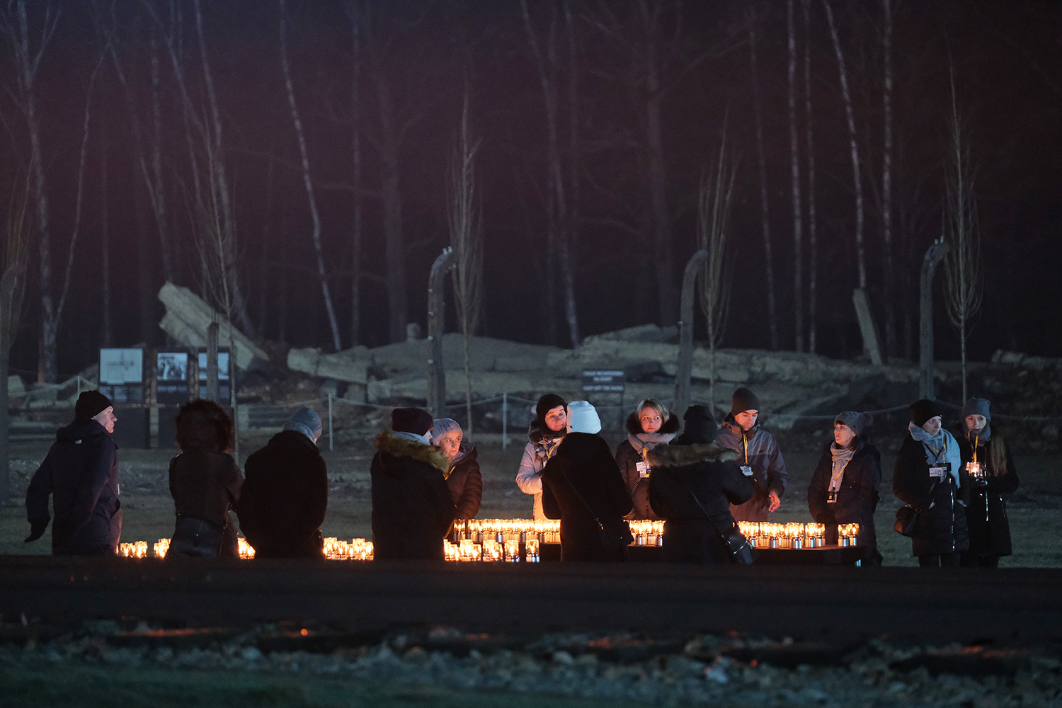 Participants stand at candles near railroad tracks as ruins of a gas chamber lie behind at the former Auschwitz-Birkenau concentration camp during the official ceremony to mark the 75th anniversary of the liberation of the Auschwitz concentration camp on January 27, 2020 near Oswiecim, Poland