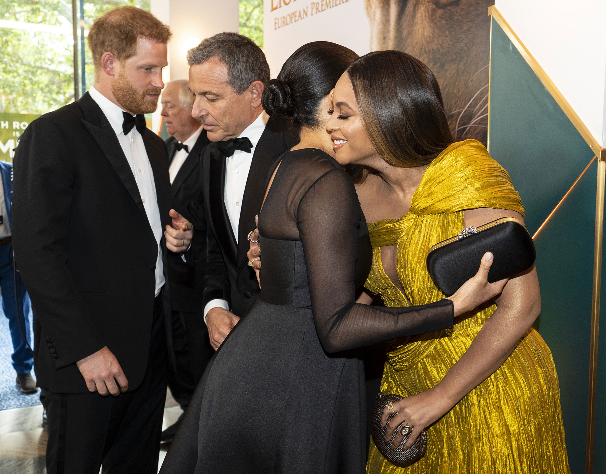Prince Harry, Duke of Sussex (L) chats with Disney CEO Robert Iger as Meghan, Duchess of Sussex (2nd R) embraces Beyonce Knowles-Carter