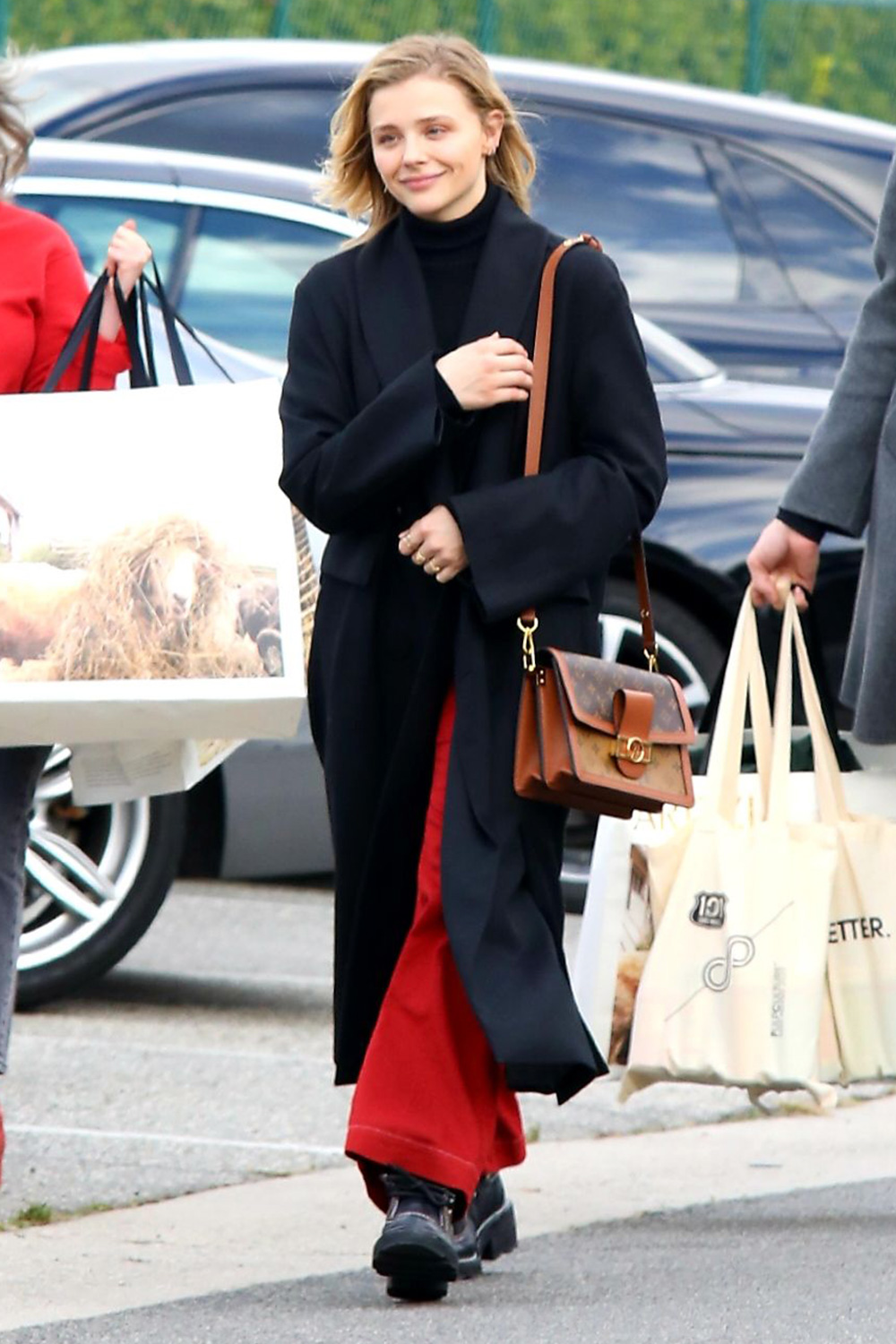 Chloe Moretz seen wearing red pants and black over coat with brother after shopping spree. 16 Jan 2020