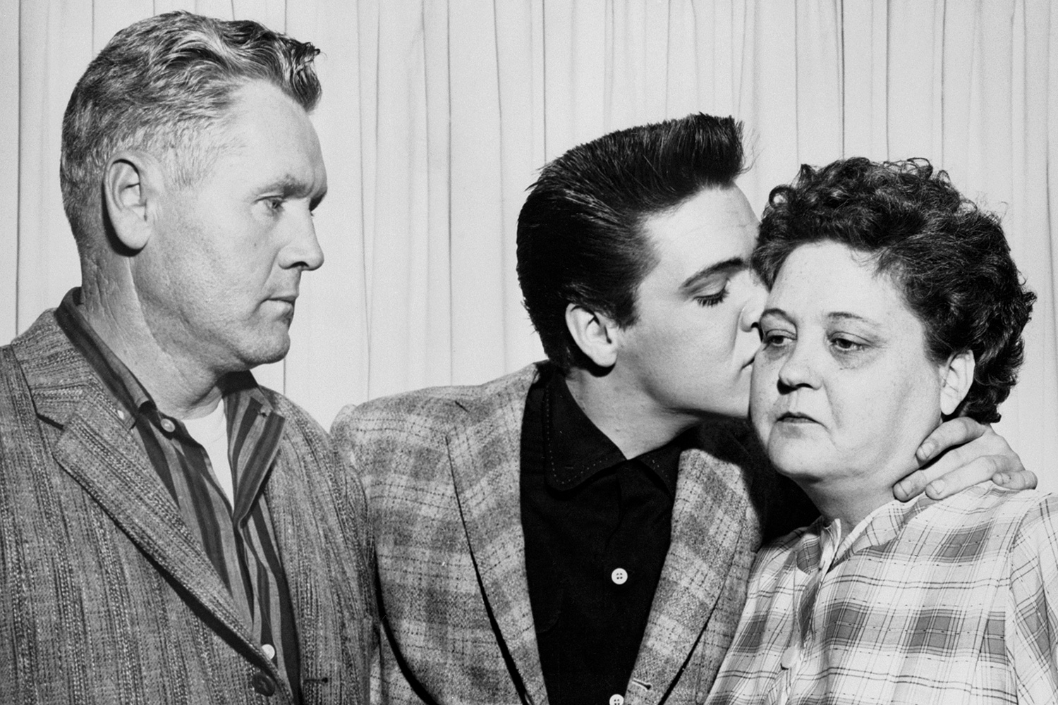 Singer Elvis Presley kisses his mother, Gladys, on the eve of his induction into the Army. At left is his father, Vernon.