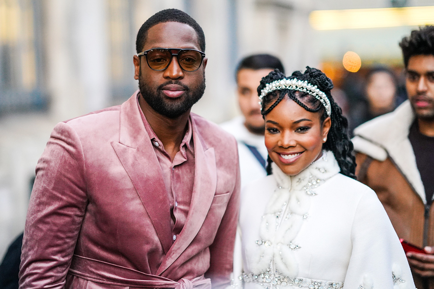 Dwayne Wade (L) wears sunglasses, a pink velvet shirt, a pink velvet jacket, a matched belt ; Gabrielle Union (R) wears a pearl headband, a white fluffy jacket with rhinestone embroideries, a mandarin collar and bell sleeves, outside Ralph & Russo, during Paris Fashion Week - Haute Couture Spring/Summer 2020, on January 20, 2020 in Paris, France